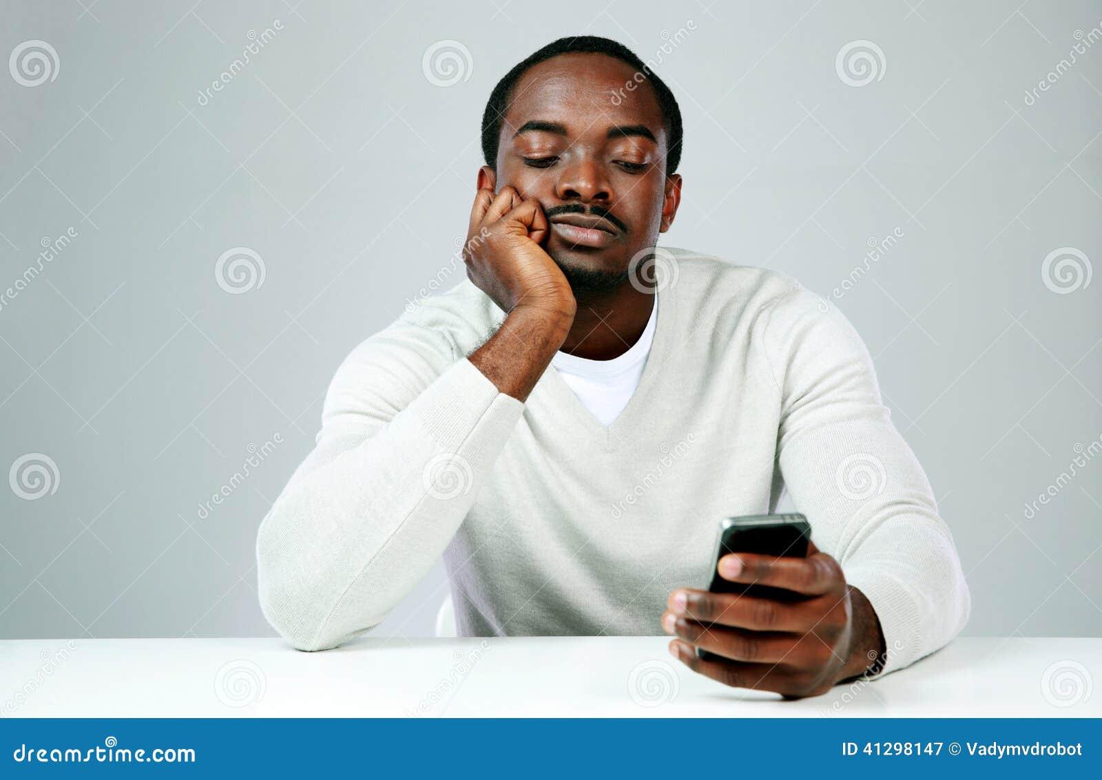 Σκεπτικό αφρικανικό άτομο που χρησιμοποιεί το smartphone