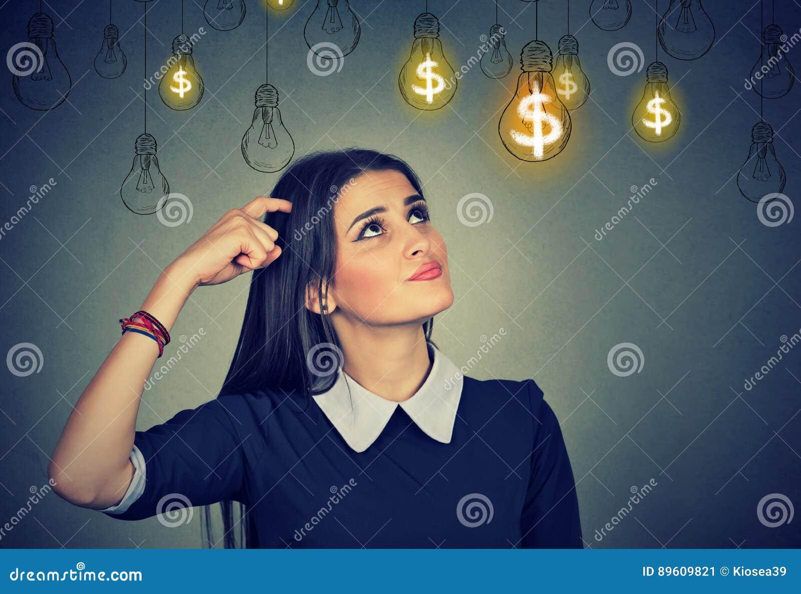 Σκεπτόμενη νέα γυναίκα που εξετάζει επάνω τις λάμπες φωτός ιδέας δολαρίων επάνω από το κεφάλι