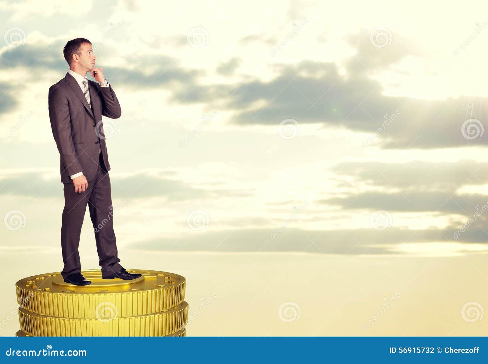 Σκεπτόμενος επιχειρηματίας που στέκεται στο σωρό νομισμάτων
