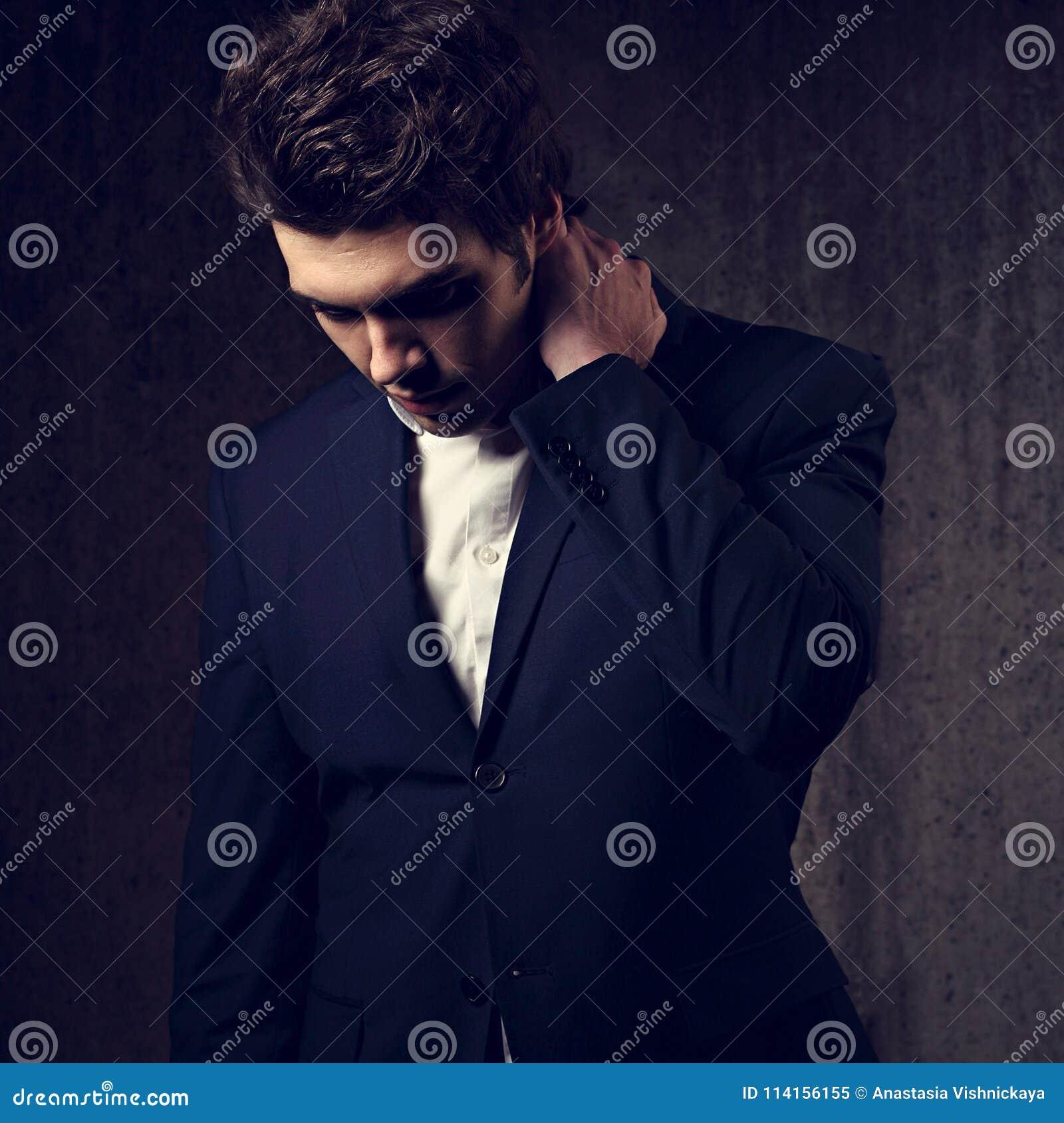 Σκεπτόμενο σοβαρό όμορφο επιχειρησιακό άτομο που κοιτάζει κάτω στα μαύρα fas