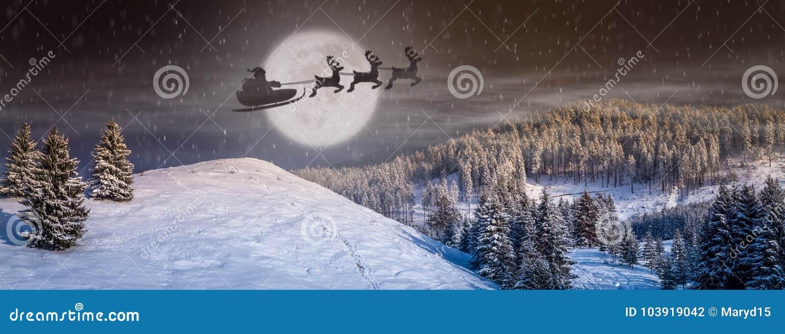 Σκηνή Παραμονής Χριστουγέννων με το δέντρο, χιόνι που πέφτει, Άγιος Βασίλης σε ένα έλκηθρο με τους ταράνδους που πετούν στον ουρα