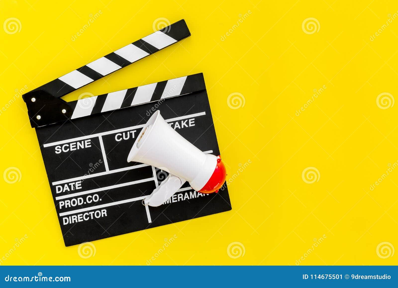 Σκηνοθέτης, έννοια παραγωγών μαγνητοσκόπηση Ηλεκτρονικό megaphone και clapperbord στο κίτρινο διάστημα άποψης υποβάθρου τοπ για