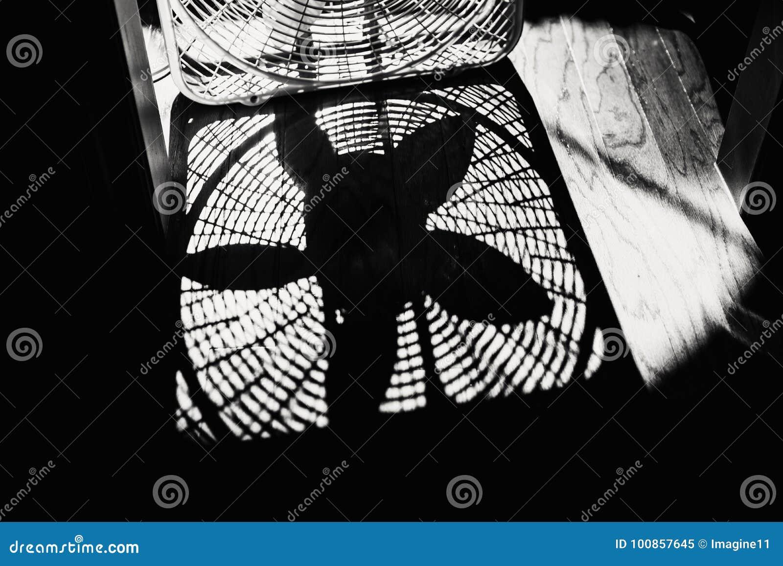 Σκιά ενός ανεμιστήρα κιβωτίων σε ένα ξύλινο πάτωμα