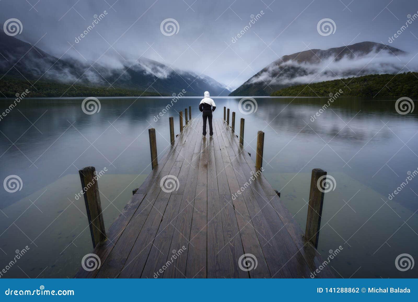 Σκιαγραφία γυναικών στη ρομαντική αποβάθρα στη λίμνη Rotoiti, άποψη που αγνοεί misty Άγιο Arnaud Ridge, όλο το μέρος των λιμνών τ
