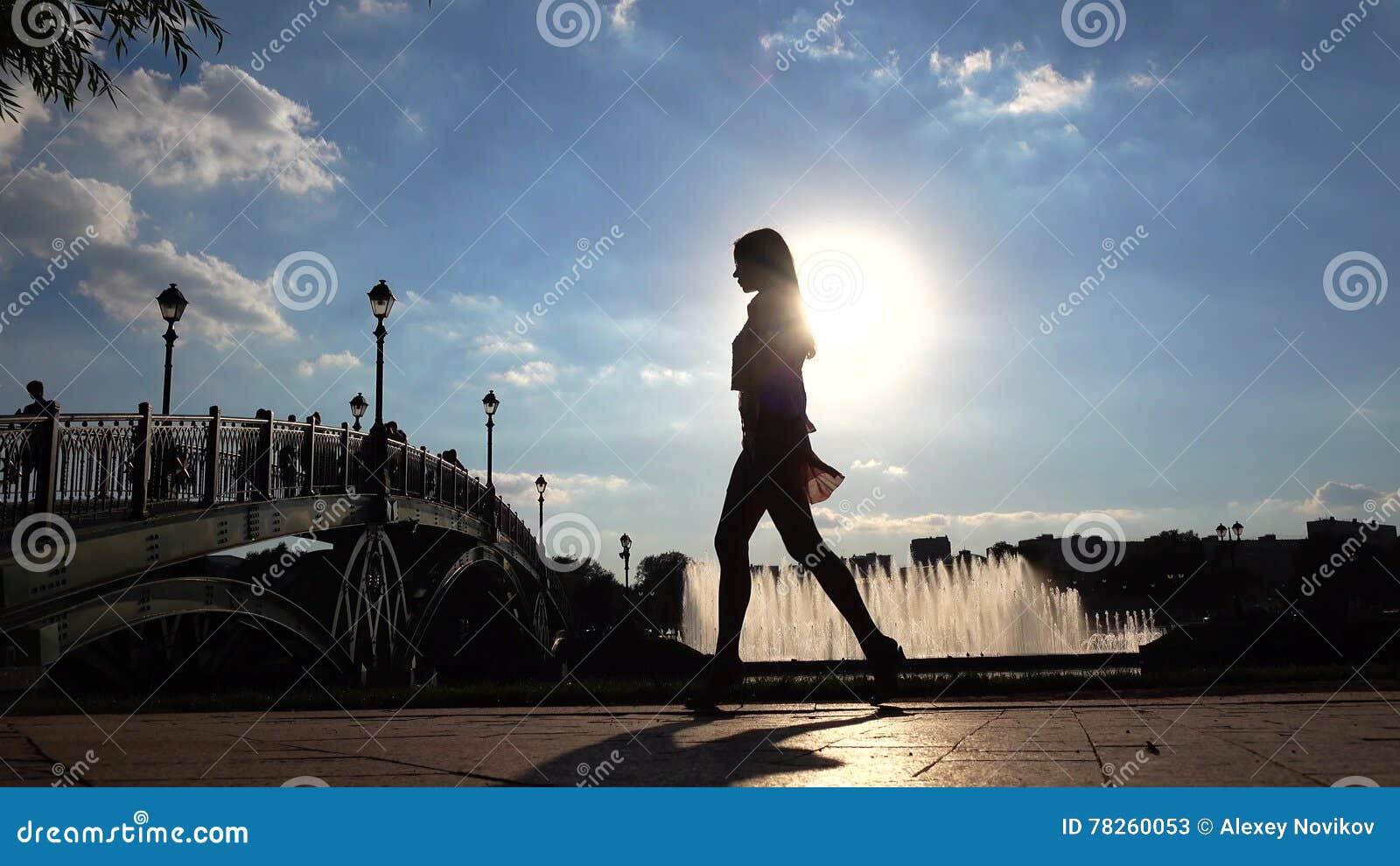Σκιαγραφία ενός λεπτού κοριτσιού στα υψηλά τακούνια που περπατά στο ηλιόλουστο ανάχωμα πάρκων