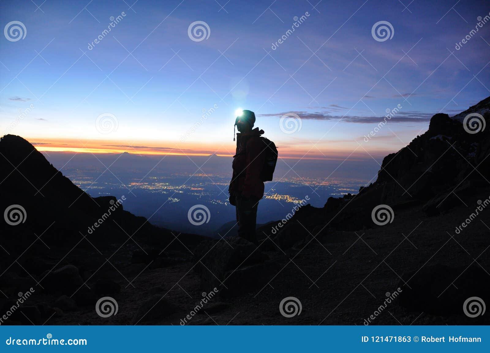 Σκιαγραφία ενός ορεσιβίου που στέκεται σε ένα βουνό μπροστά από το τ