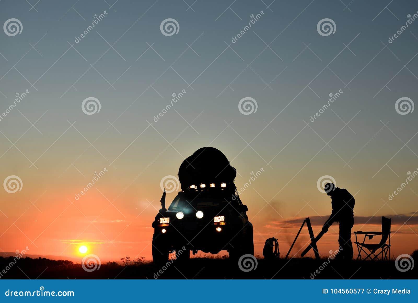 Σκιαγραφία ενός προσώπου που στρατοπεδεύει με ένα αυτοκίνητο