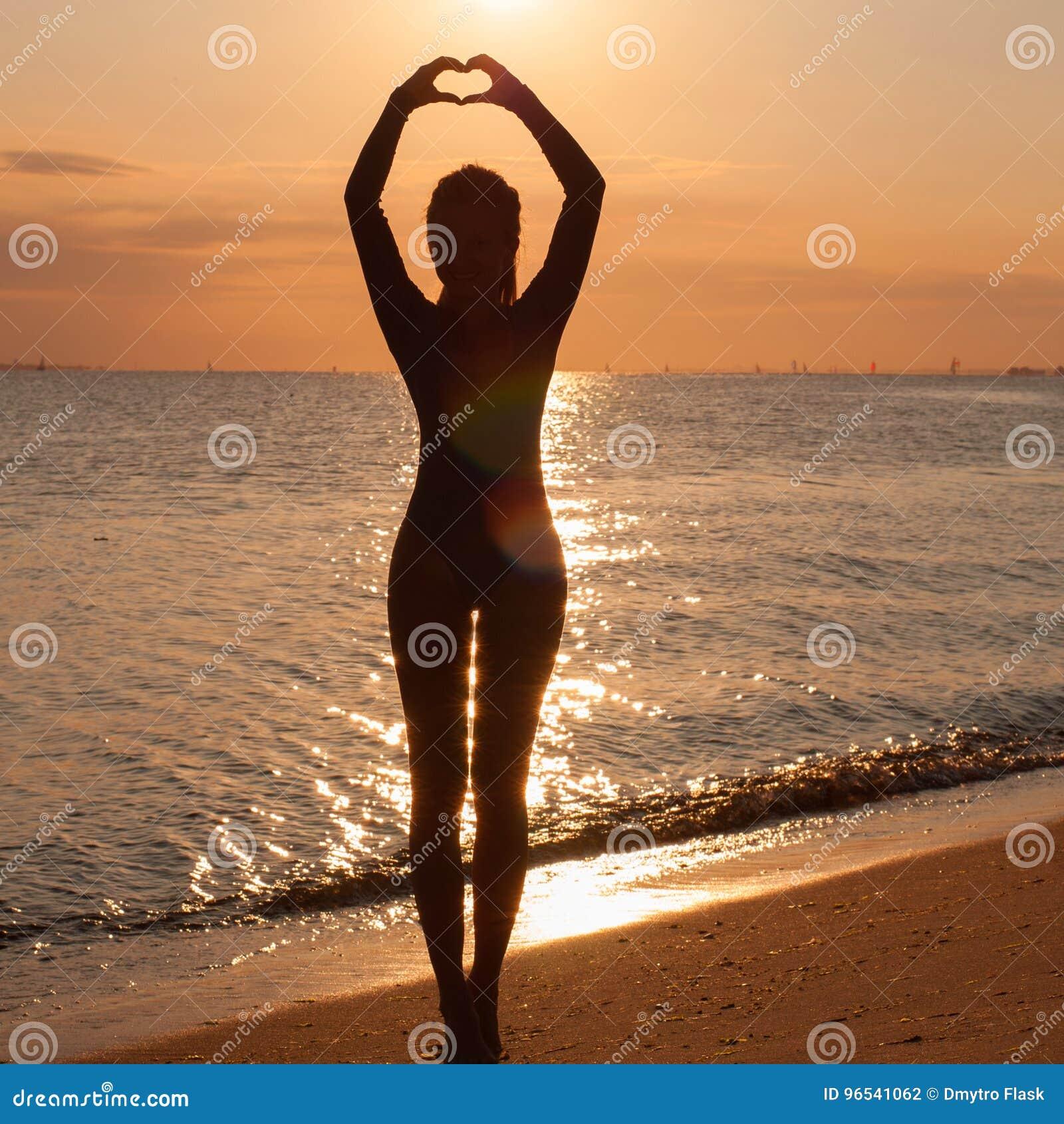 Σκιαγραφία μιας νέας γιόγκας άσκησης γυναικών στην παραλία στο ηλιοβασίλεμα