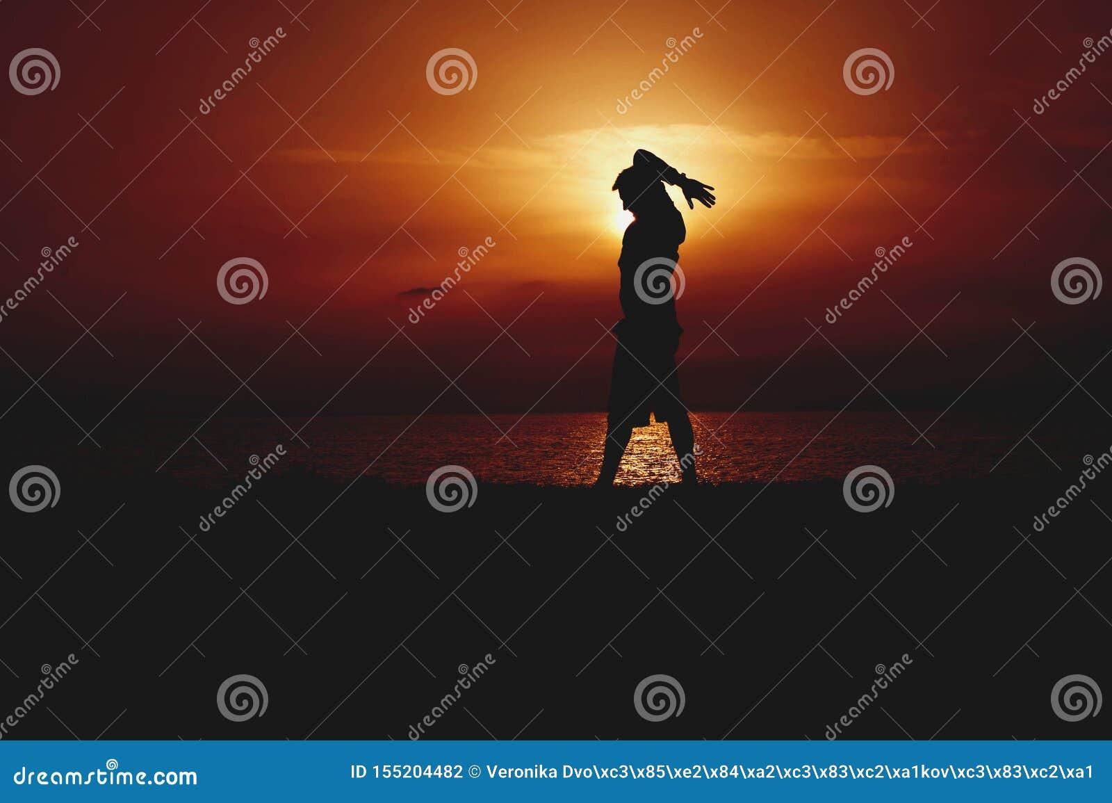 Σκιαγραφία της γιόγκας άσκησης νεαρών άνδρων Πορτοκαλί ηλιοβασίλεμα Seacoast