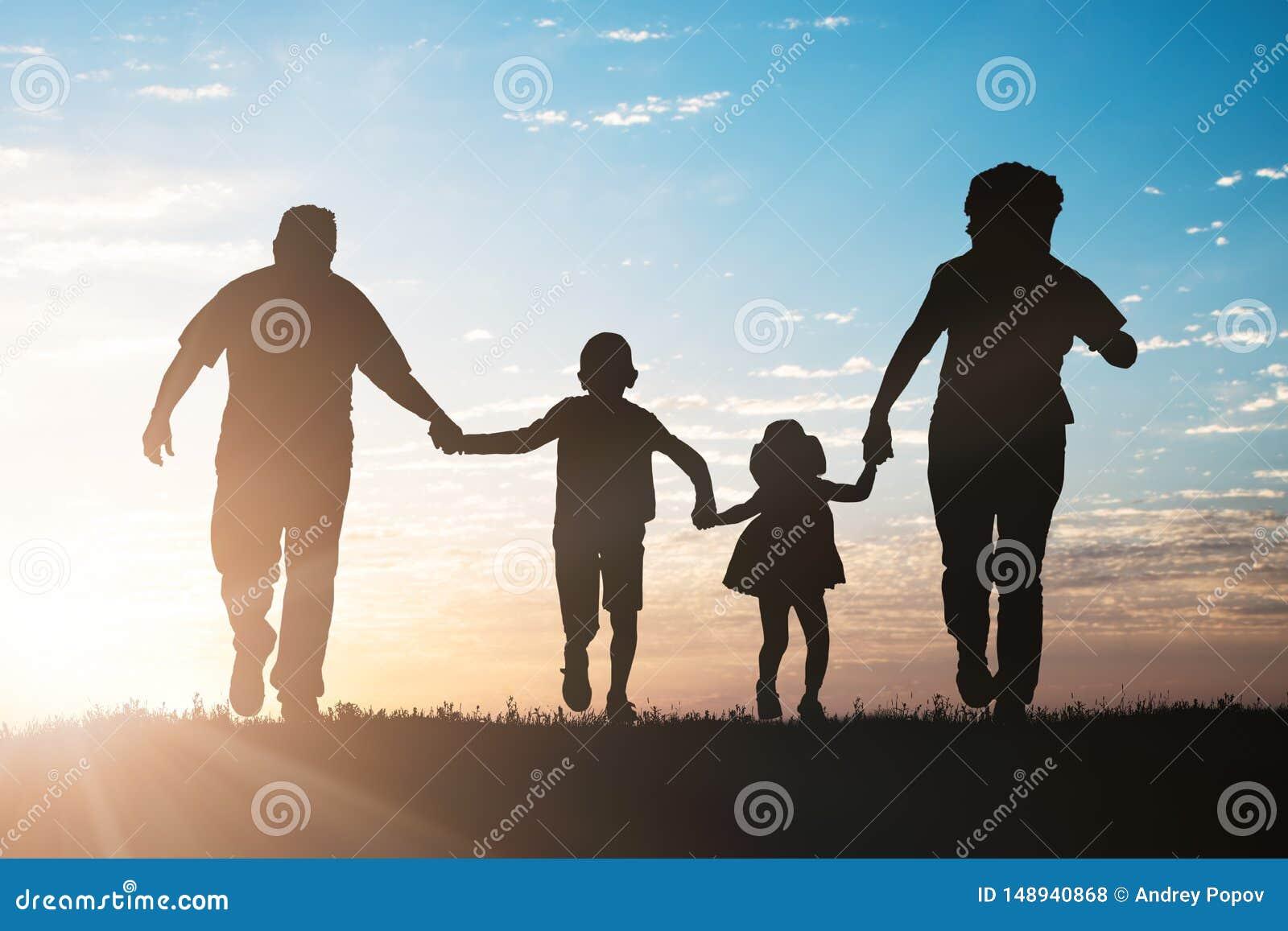Σκιαγραφία της οικογένειας που τρέχει στο πάρκο