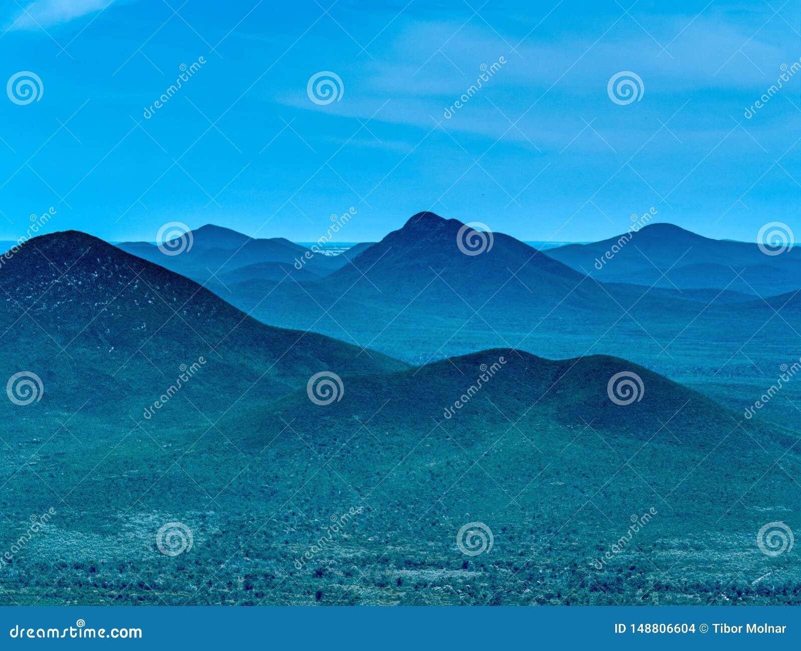 Σκιαγραφία τοπίων βουνών, στρώματα των κοιλάδων και μπλε ουρανός λόφων στο υπόβαθρο