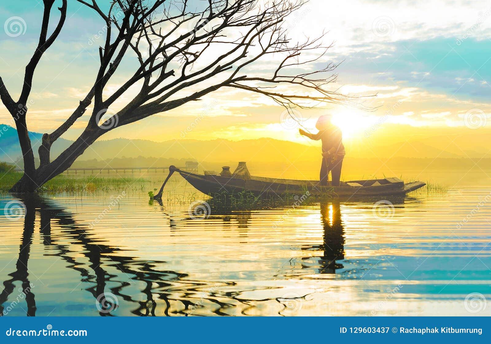 Σκιαγραφία του ψαρά που χρησιμοποιεί το δίχτυ ψαρέματος που στέκεται στο αυτί μικρών βαρκών