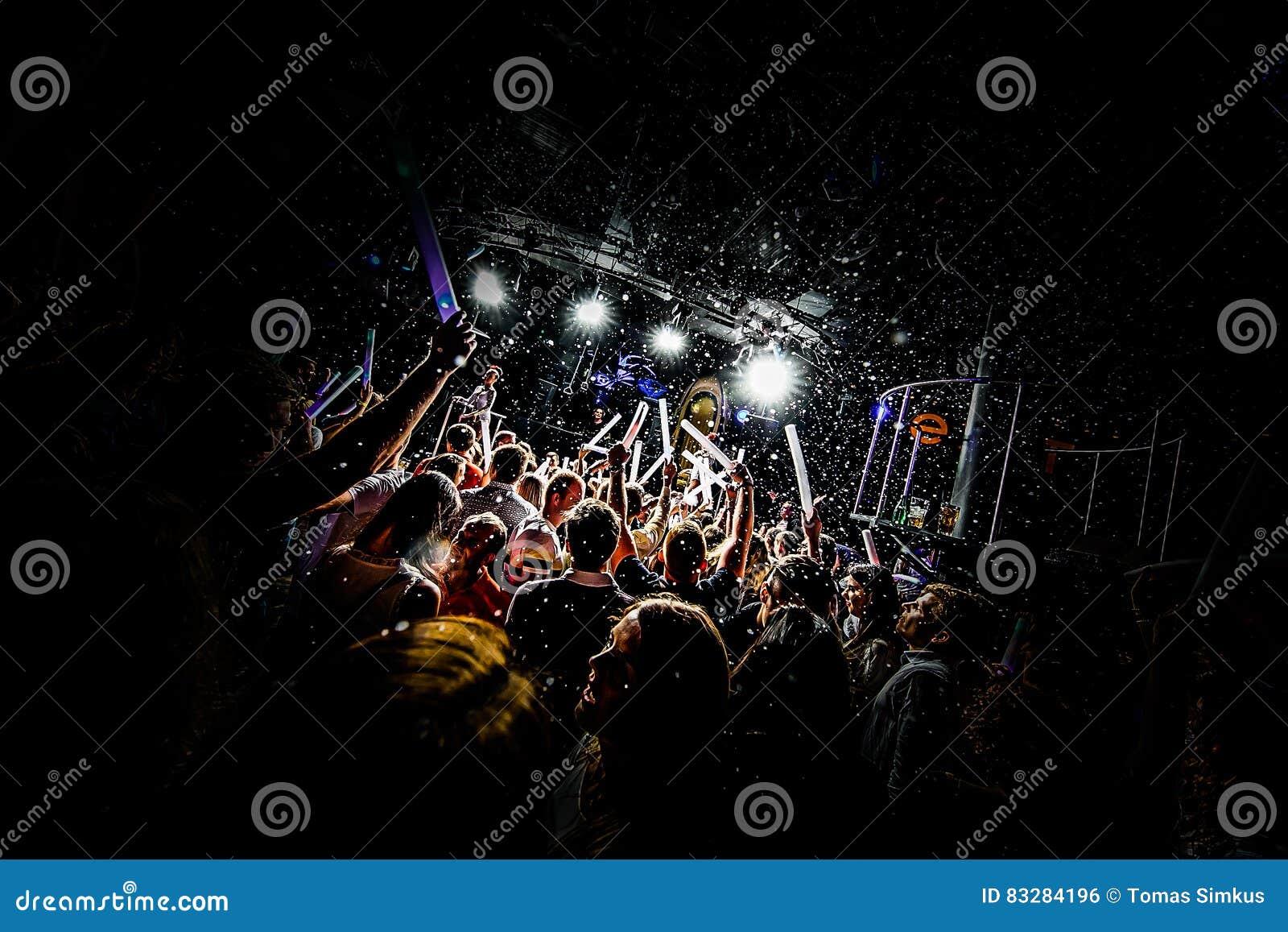 Σκιαγραφίες του πλήθους συναυλίας μπροστά από τα φωτεινά φω τα σκηνών με το κομφετί