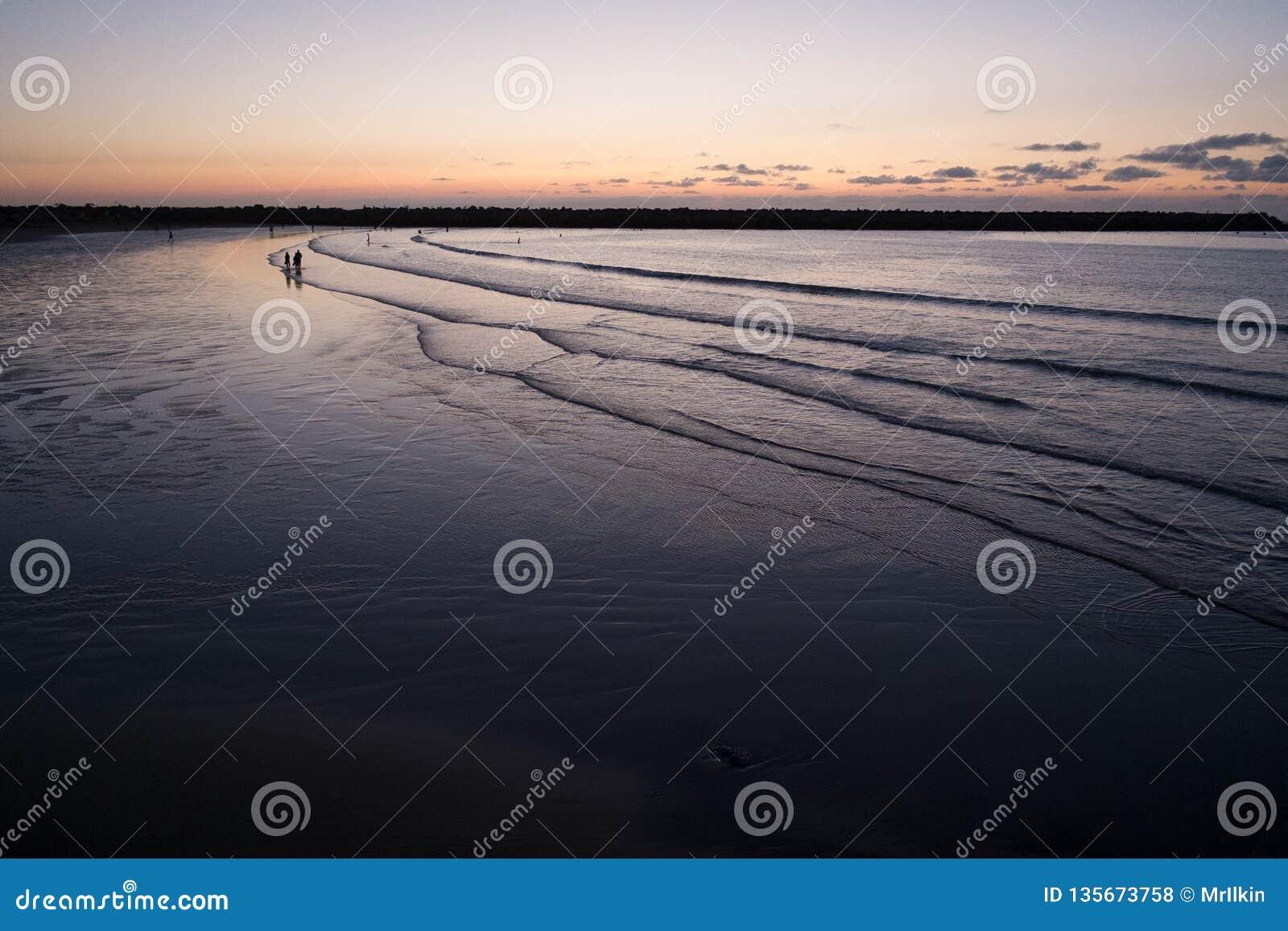 Σκιαγραφίες των ανθρώπων στην παραλία βραδιού