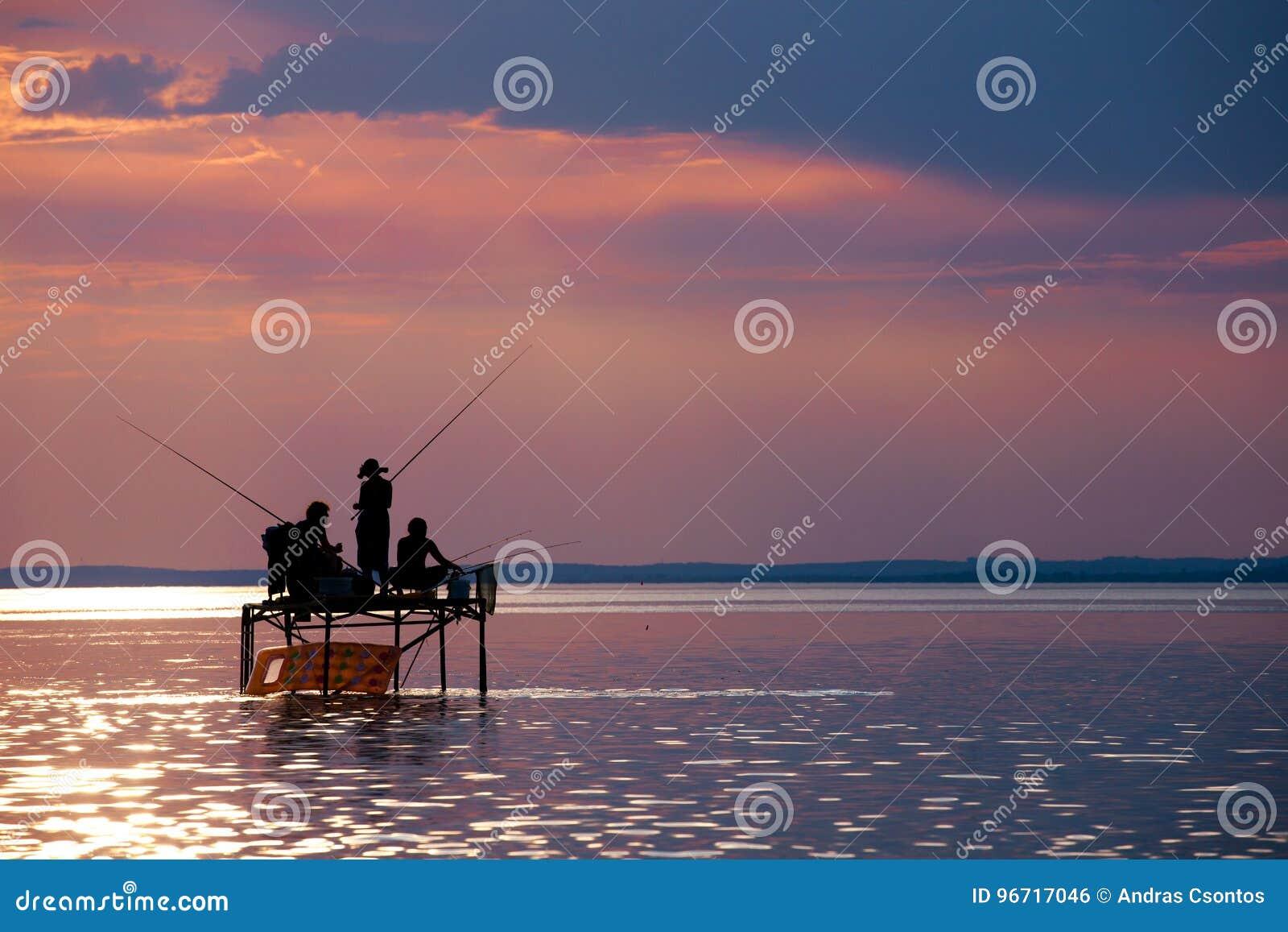Σκιαγραφίες ψαράδων ` σε μια στάση αλιείας στο ηλιοβασίλεμα στη λίμνη Balat