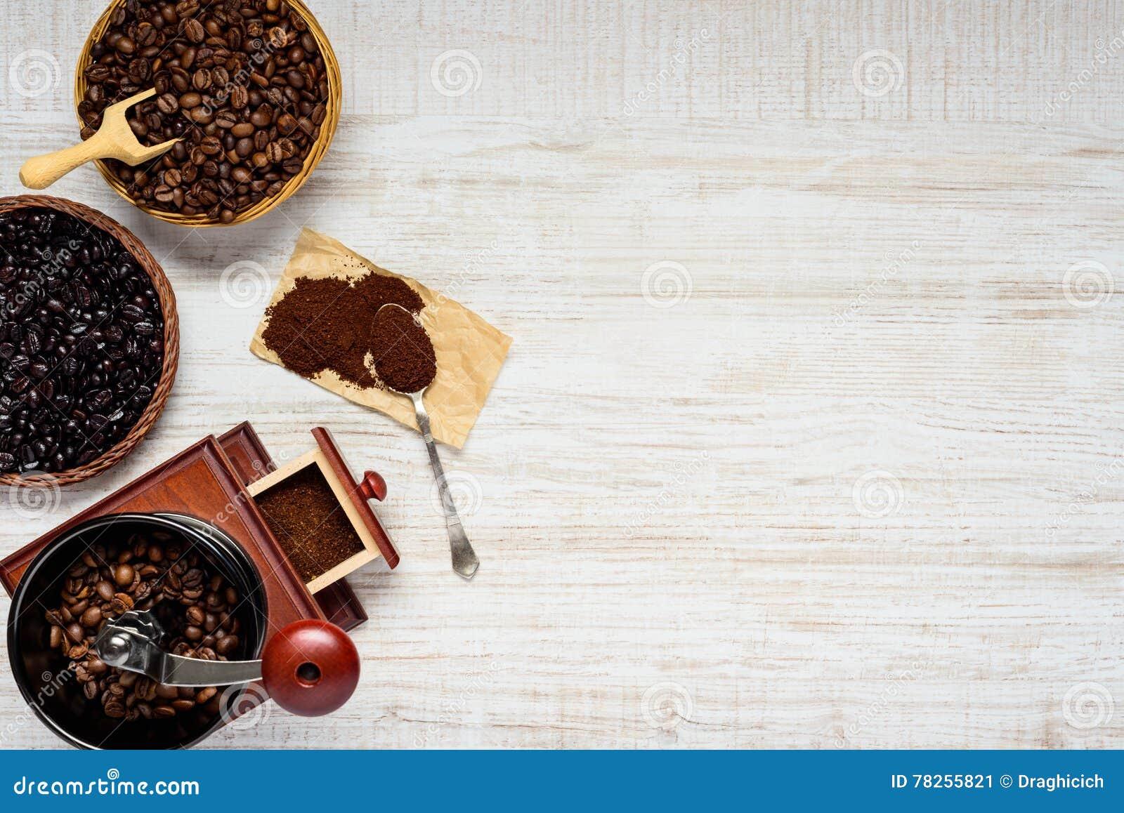 Σκοτεινά και καφετιά φασόλια καφέ με το μύλο στο διάστημα αντιγράφων