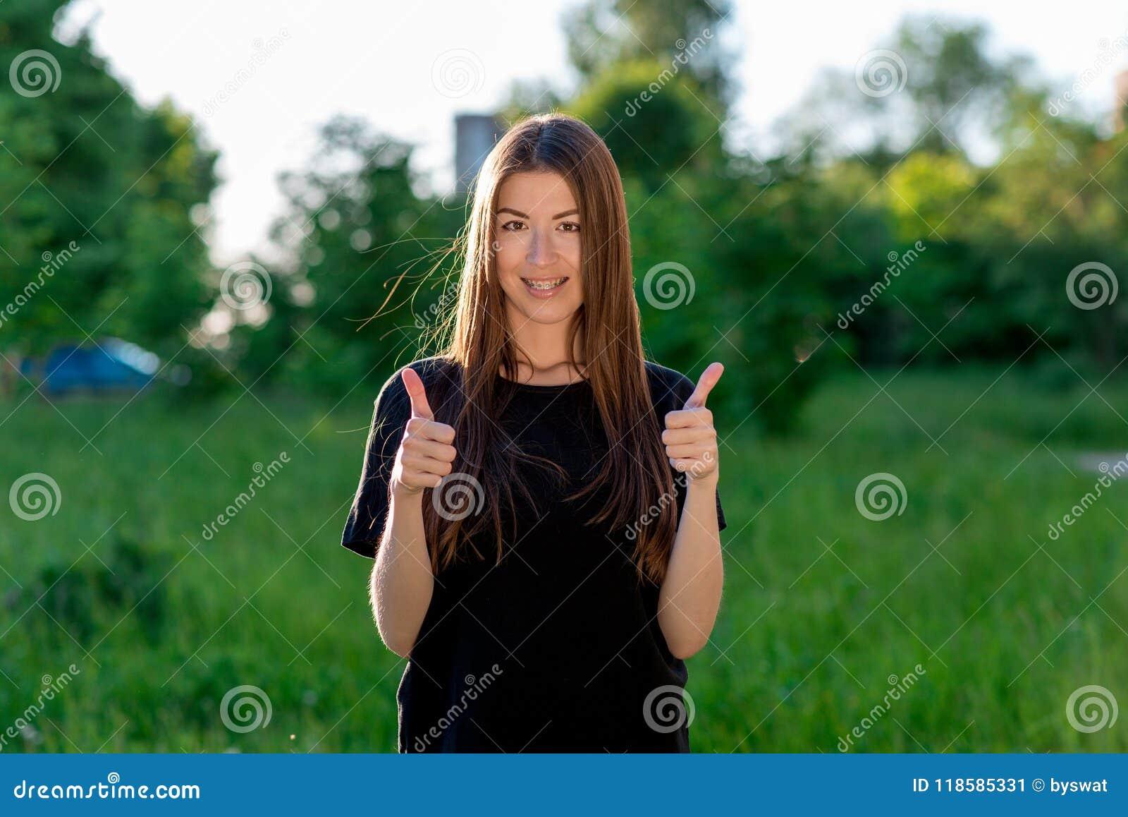 Σκοτεινός-μαλλιαρό καφετής-eyed κορίτσι Ασιάτης Το καλοκαίρι υπαίθρια Δείχνει το δάχτυλό του επάνω και με τα δύο χέρια Συγκίνηση