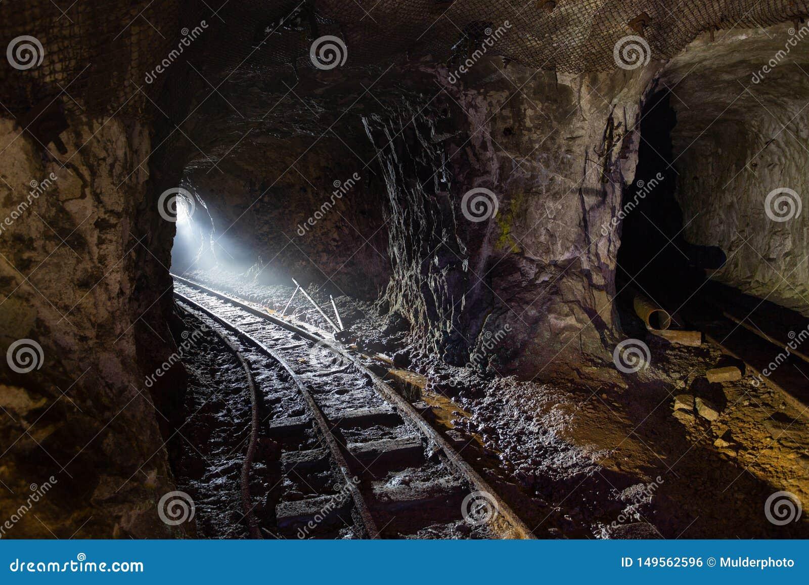 Σκοτεινό βρώμικο εγκαταλειμμένο ορυχείο ουράνιου με τα σκουριασμένα υπόλοιπα του σιδηροδρόμου