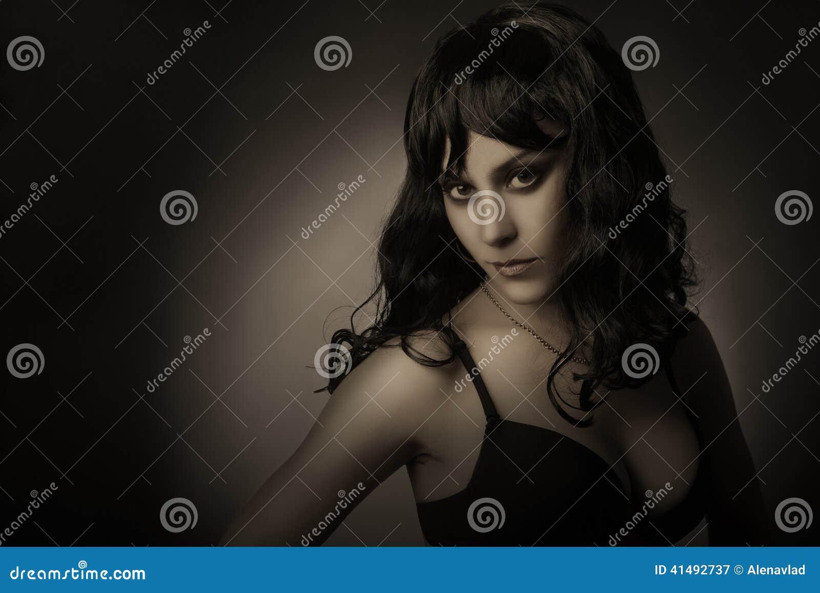 Σκοτεινό πορτρέτο της κομψής γυναίκας brunette