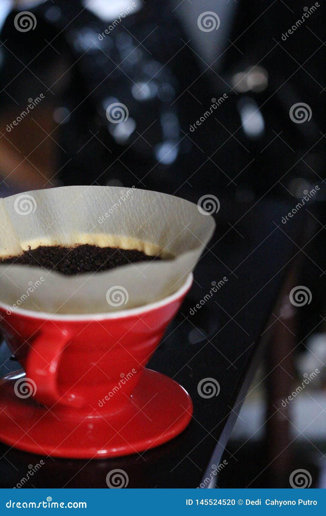 Σκόνη καφέ που θα παρασκευαστεί με ένα κόκκινο φλυτζάνι