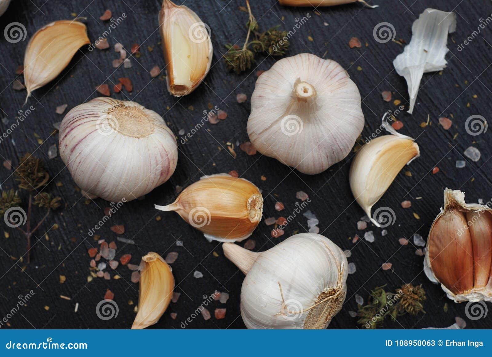 Σκόρδο με τα καρυκεύματα στο σκοτεινό υπόβαθρο συστατικά τροφίμων για τη συνταγή και την προετοιμασία τροφίμων Άλας και έγγραφο