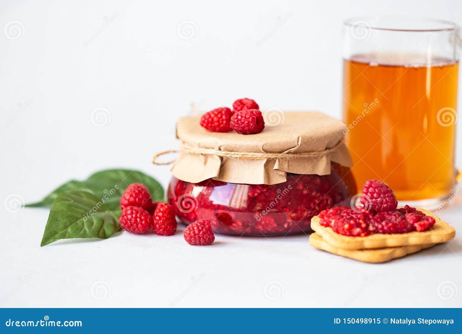 Σμέουρα με τη ζάχαρη, υγιή φρέσκα σμέουρα, σπιτική μαρμελάδα σε ένα βάζο, πρόγευμα πρωινού σε ένα ελαφρύ υπόβαθρο