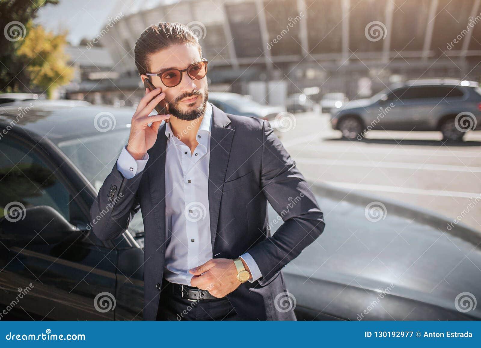 Σοβαρές και συγκεντρωμένες νέες στάσεις επιχειρηματιών στο αυτοκίνητο και συζητήσεις στο τηλέφωνο Φορά τα γυαλιά ηλίου Ο τύπος κο