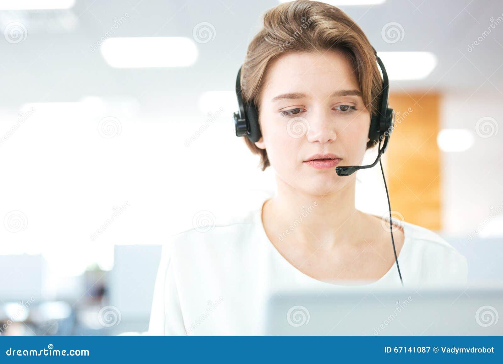 Σοβαρή αρκετά νέα γυναίκα που εργάζεται ως τηλεφωνικός χειριστής υποστήριξης