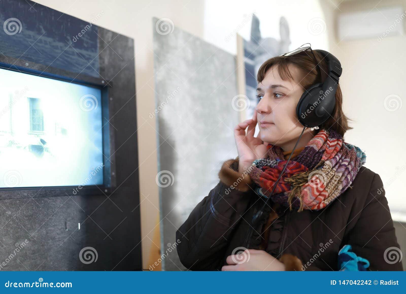 Σοβαρή γυναίκα στα ακουστικά που προσέχει τον κινηματογράφο