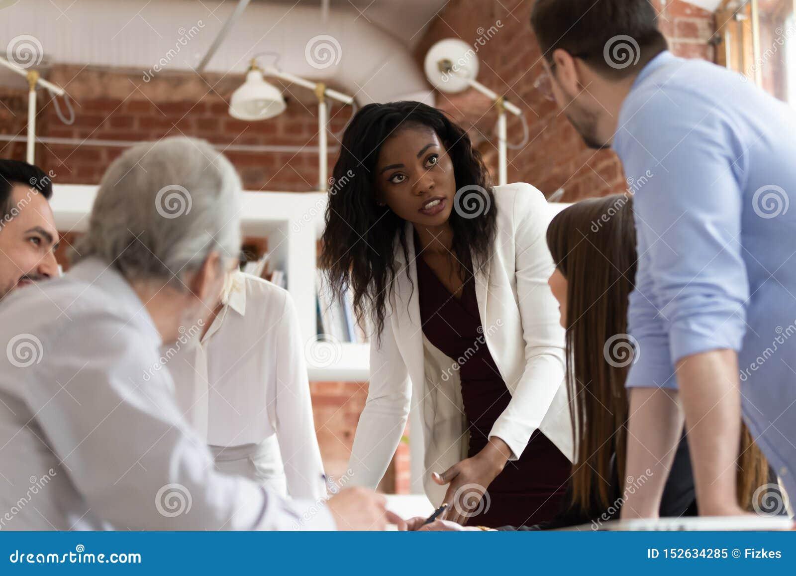 Σοβαρή θηλυκή μαύρη εκτελεστική συζήτηση με τον άνδρα συνάδελφος στην ενημέρωση