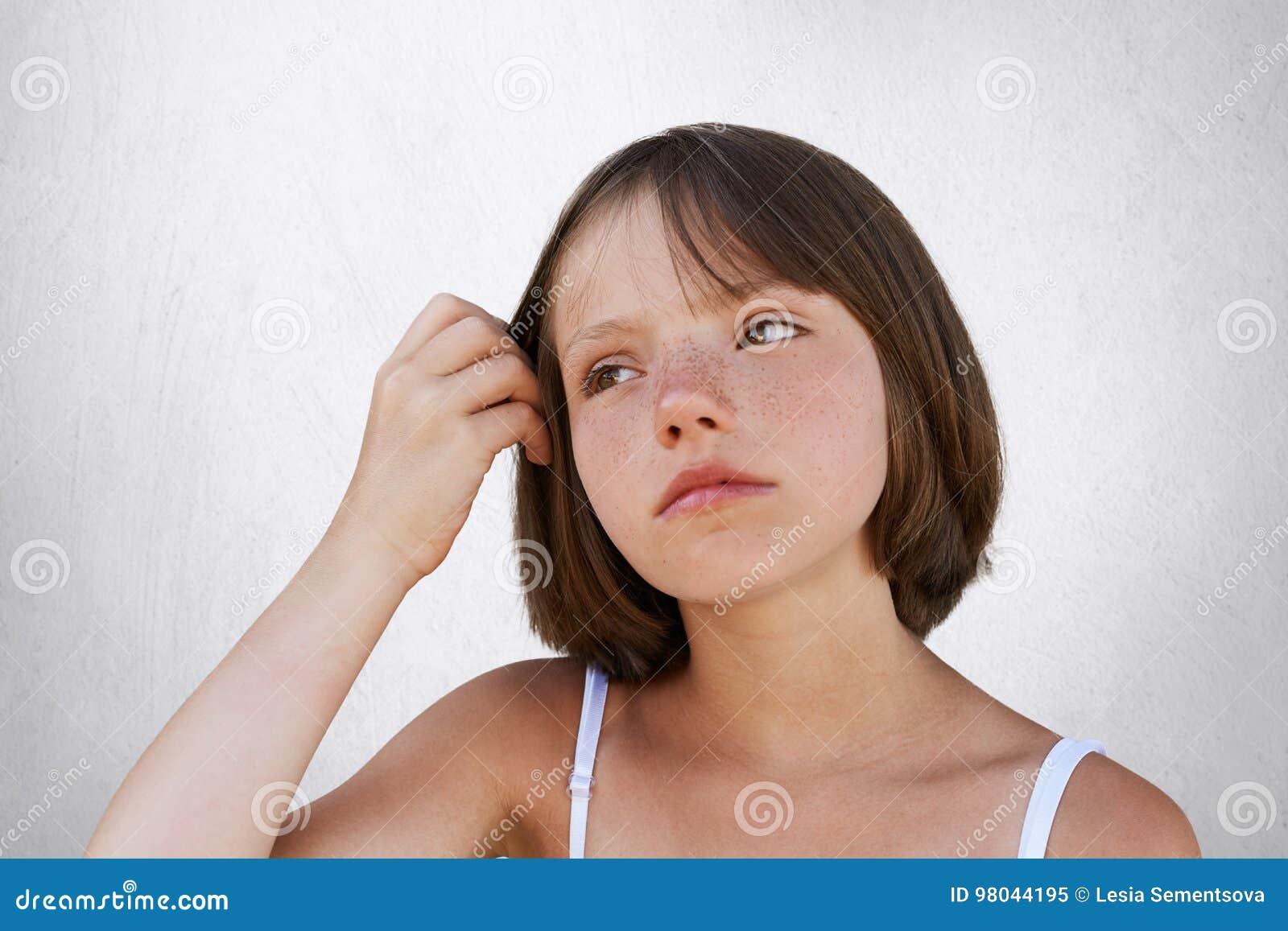 Σοβαρός λίγο φακιδοπρόσωπο παιδί, που κρατά το χέρι της στην τρίχα, στοχαστική έκφραση havin, που κοιτάζει κατά μέρος Όμορφη τοπο