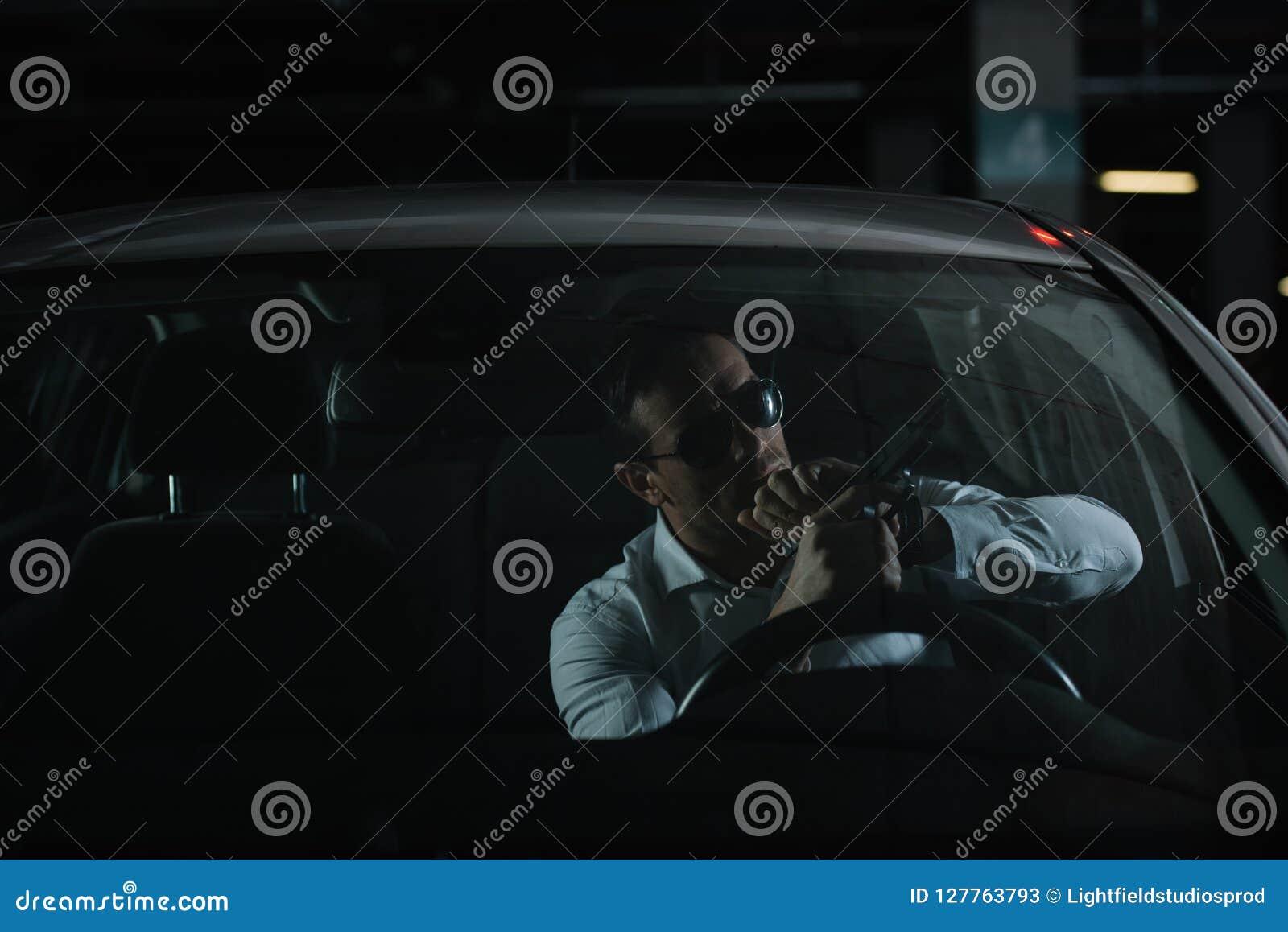 σοβαρός αρσενικός μυστικός αξιωματούχος στα γυαλιά ηλίου που χρεώνει το πυροβόλο όπλο
