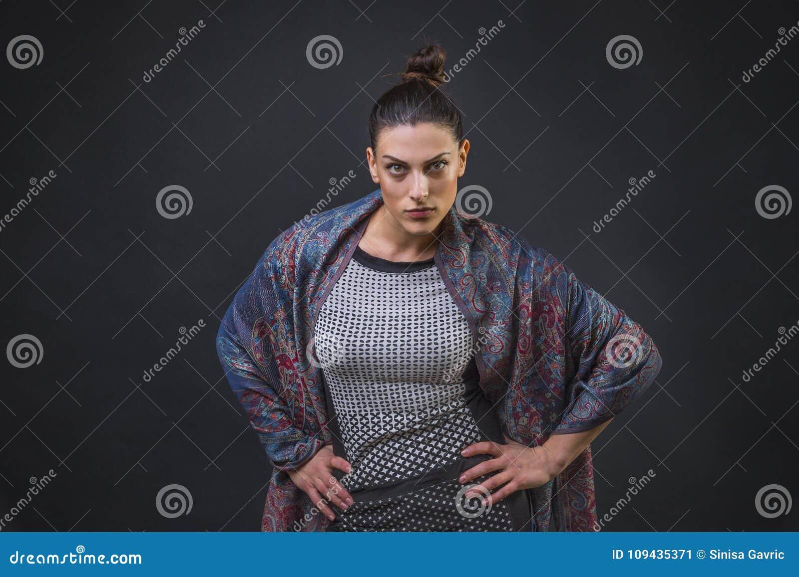 Σοβαρός και εξουσιάζοντας κοιτάξτε επίμονα μιας νέας ελκυστικής γυναίκας με τα όπλα της στα ισχία της