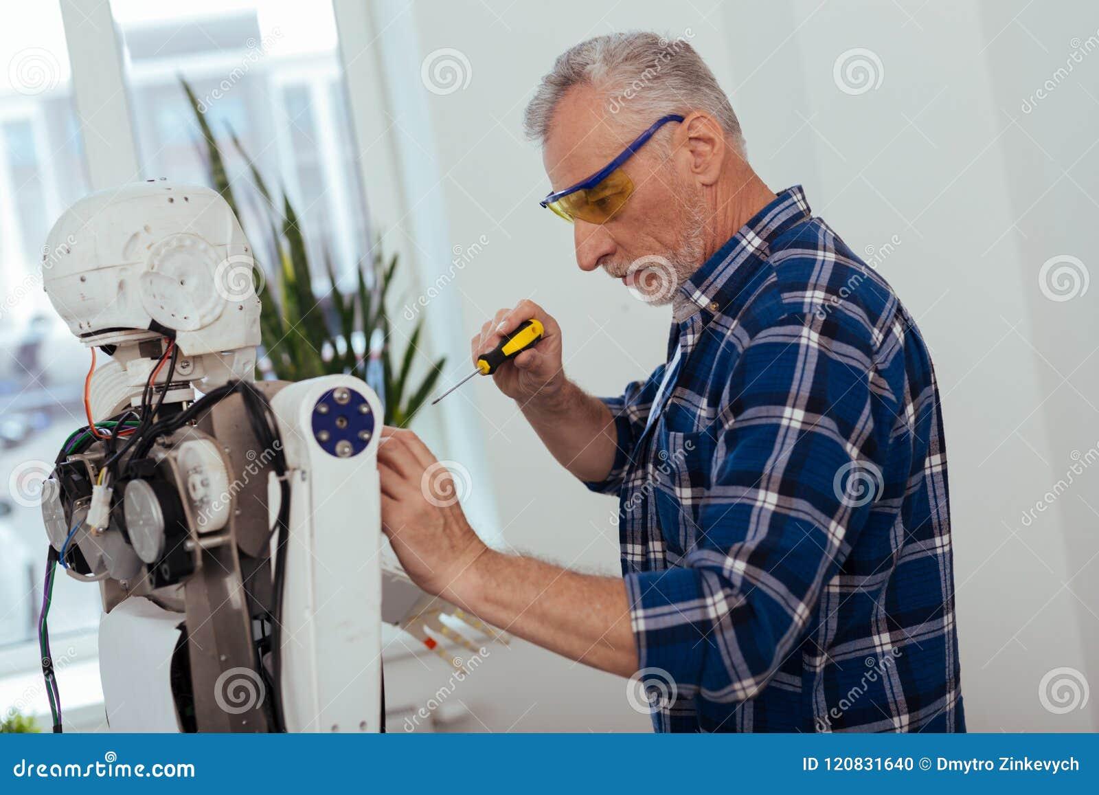 Σοβαρό ηλικιωμένο άτομο που στέκεται κοντά στο ρομπότ