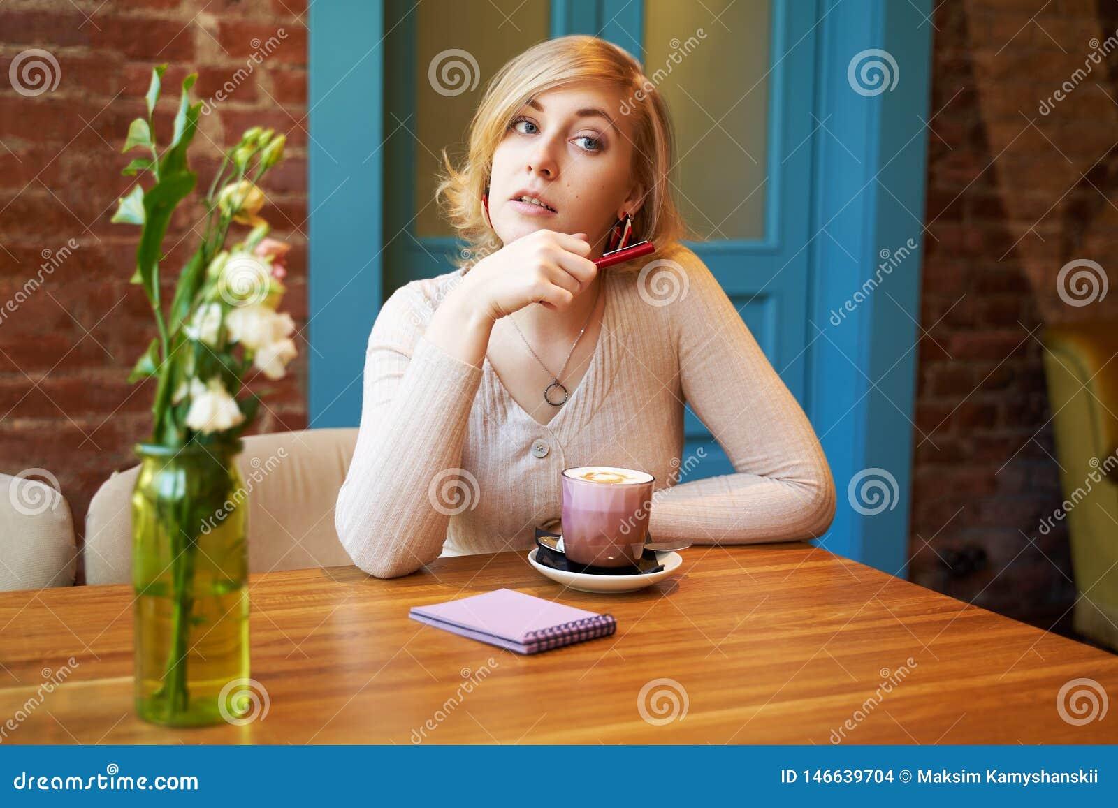 Σοβαρό στοχαστικό κορίτσι που εξετάζει τη κάμερα r