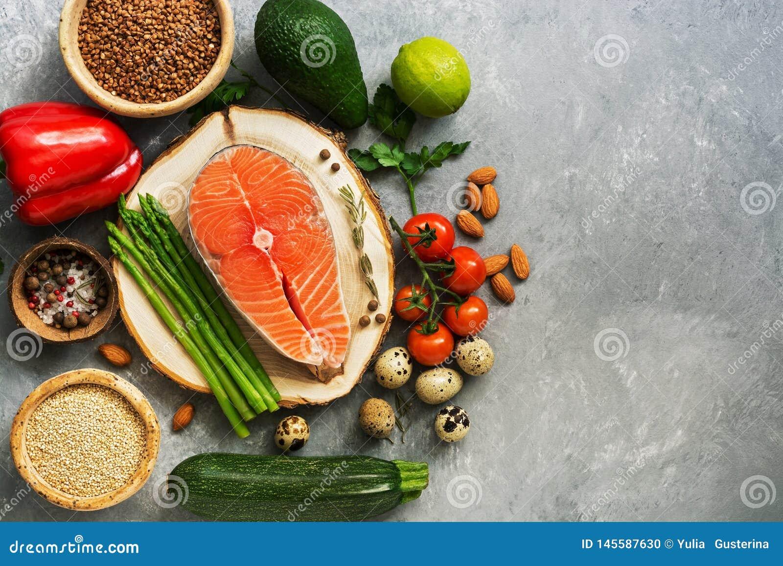Σολομός μπριζόλας ακατέργαστων ψαριών, δημητριακά, φρέσκα λαχανικά, αυγό ορτυκιών, καρύδια και καρυκεύματα σε ένα γκρίζο υπόβαθρο