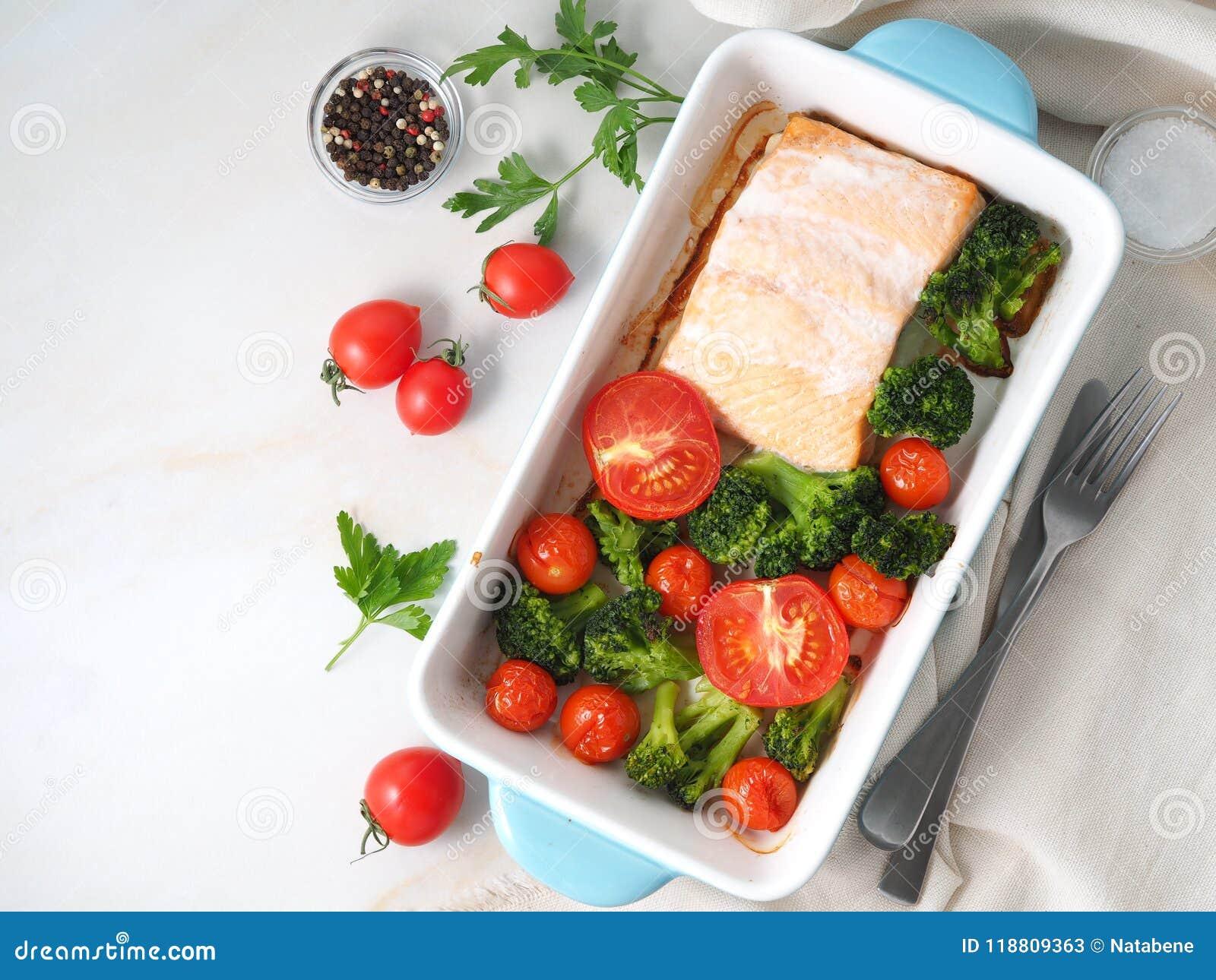 Σολομός ψαριών που ψήνεται στο φούρνο με τα λαχανικά - μπρόκολο, ντομάτες Υγιή τρόφιμα διατροφής, άσπρο μαρμάρινο σκηνικό, τοπ άπ