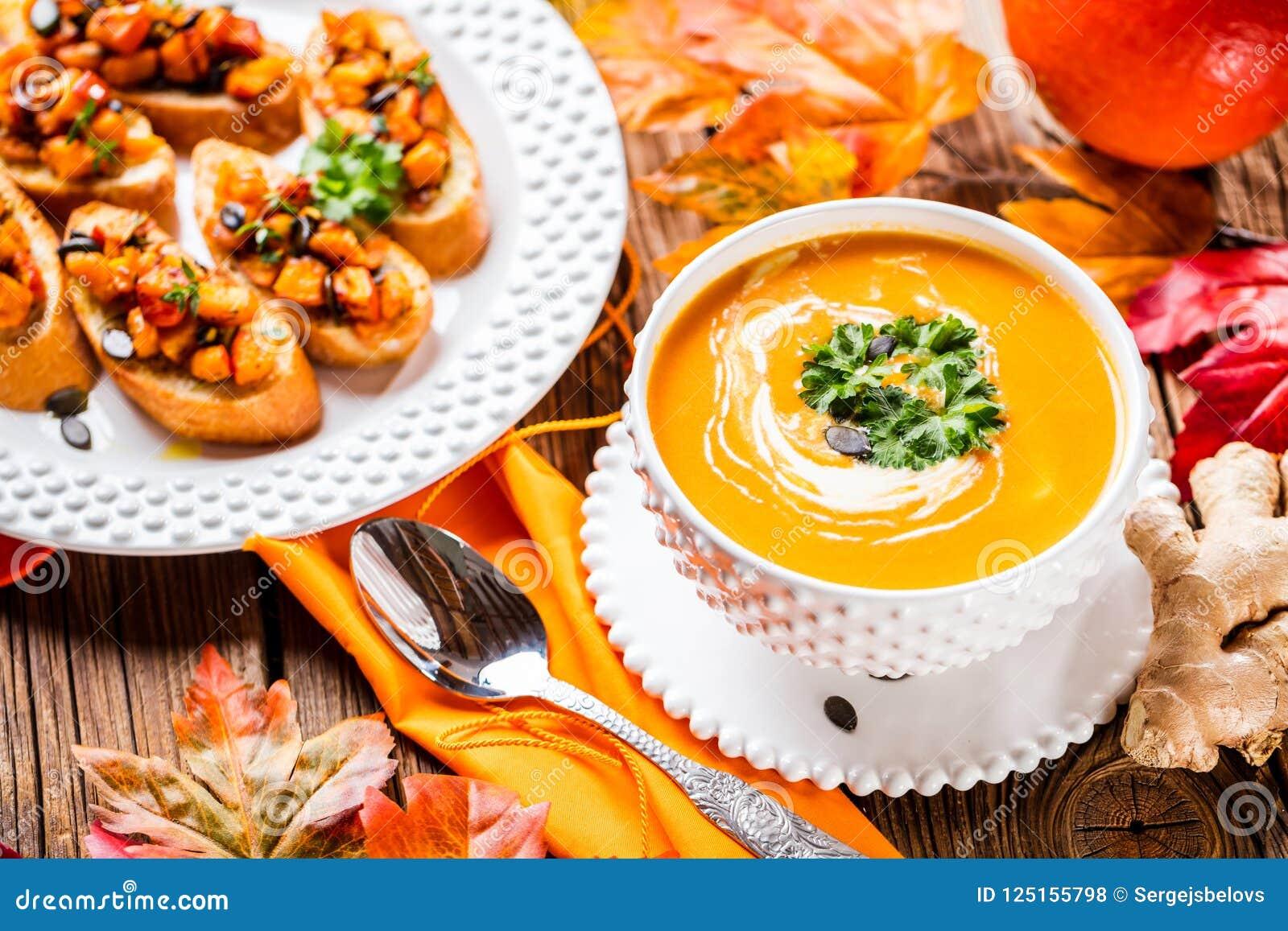 Σούπα κολοκύθας φθινοπώρου που εξυπηρετείται σε ένα άσπρο πιάτο με το brushetta κολοκύθας
