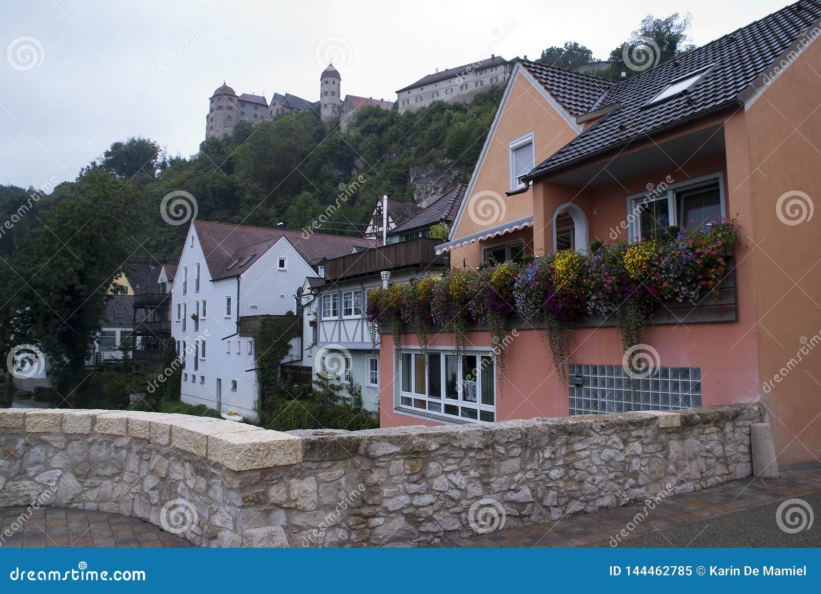 Σπίτια κατά μήκος του ποταμού με το κάστρο στο υπόβαθρο
