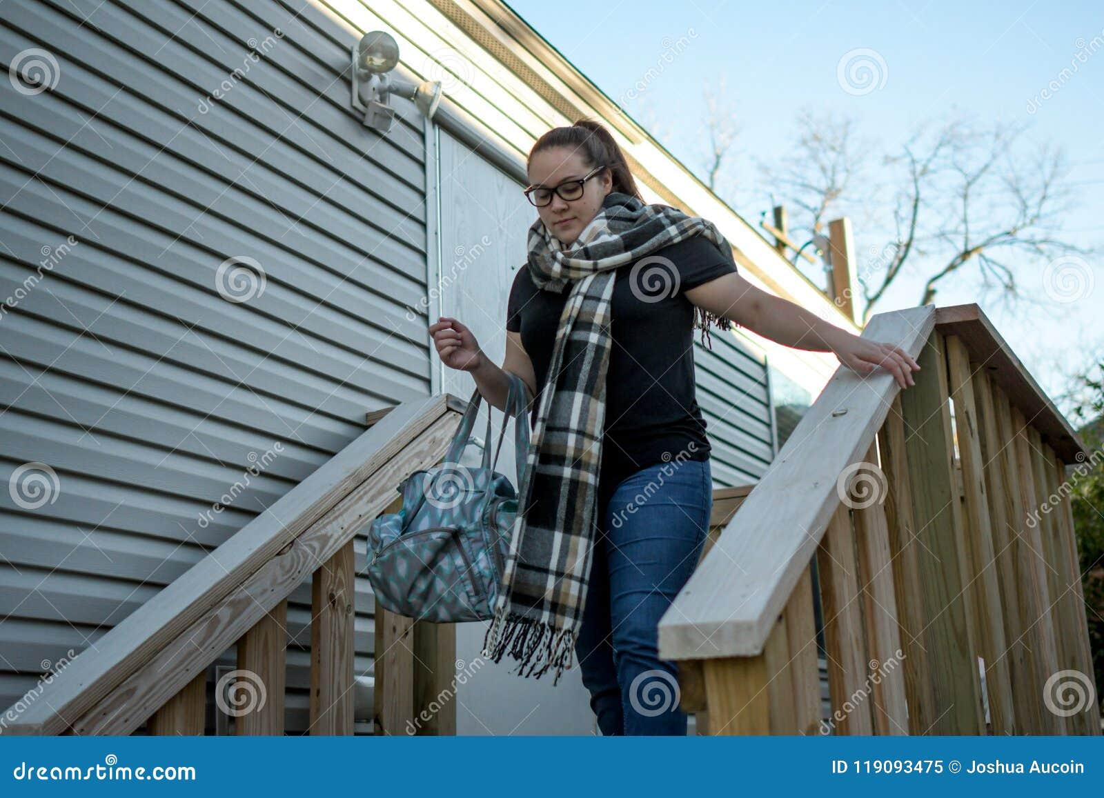 Σπίτι φύλλων γυναικών με την τσάντα ντυμένη πέρα από το βραχίονά της