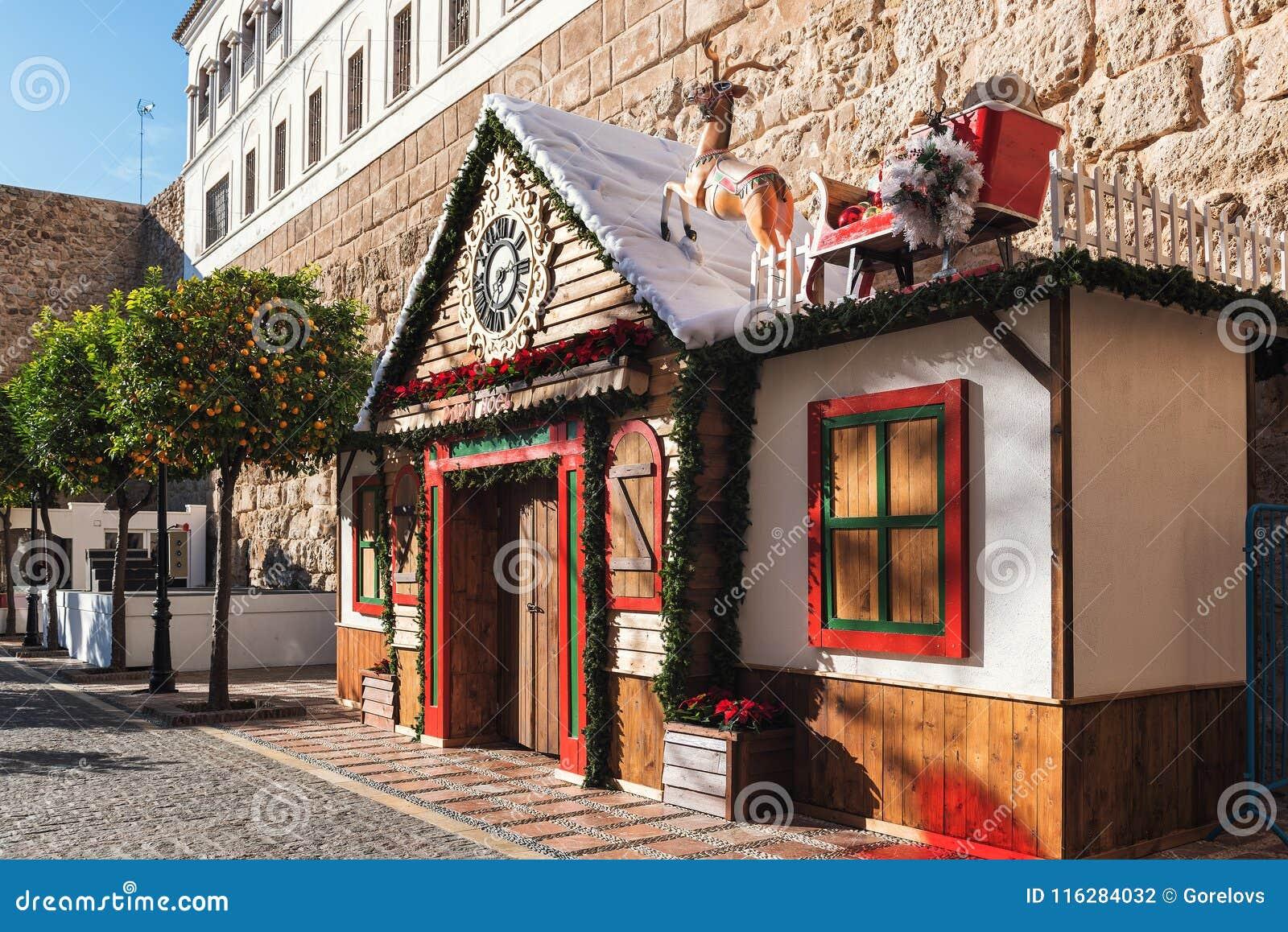 Σπίτι Χριστουγέννων που διακοσμείται με το έλκηθρο Santa ` s στη στέγη στο κεντρικό τετράγωνο της πόλης