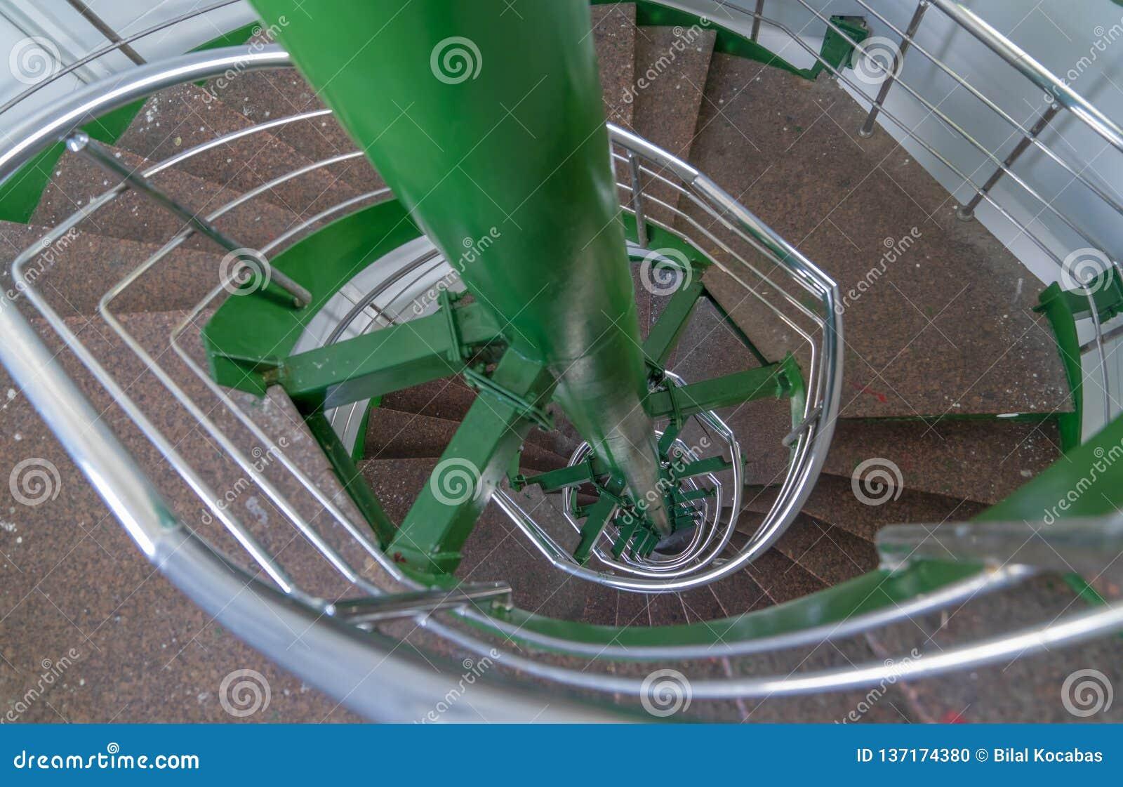 Σπειροειδές κλιμακοστάσιο πολυ-πτήσης με τα κιγκλιδώματα μετάλλων που βλέπουν από την κορυφή της σκάλας