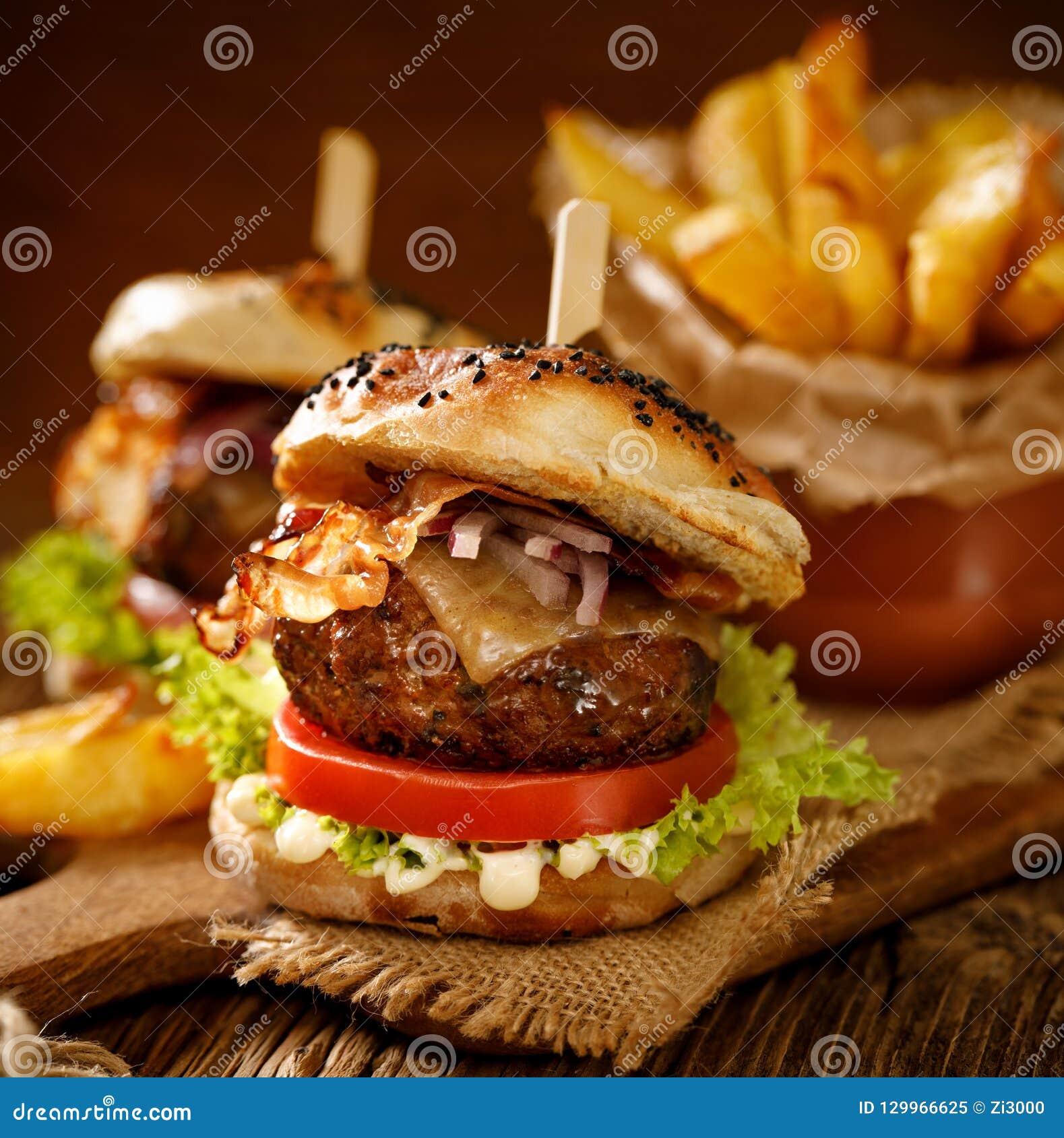 Σπιτικά burgers με το ψημένο στη σχάρα μπέϊκον, το κόκκινο κρεμμύδι, το φρέσκο μαρούλι, τα τουρσιά αγγουριών, την ντομάτα και την