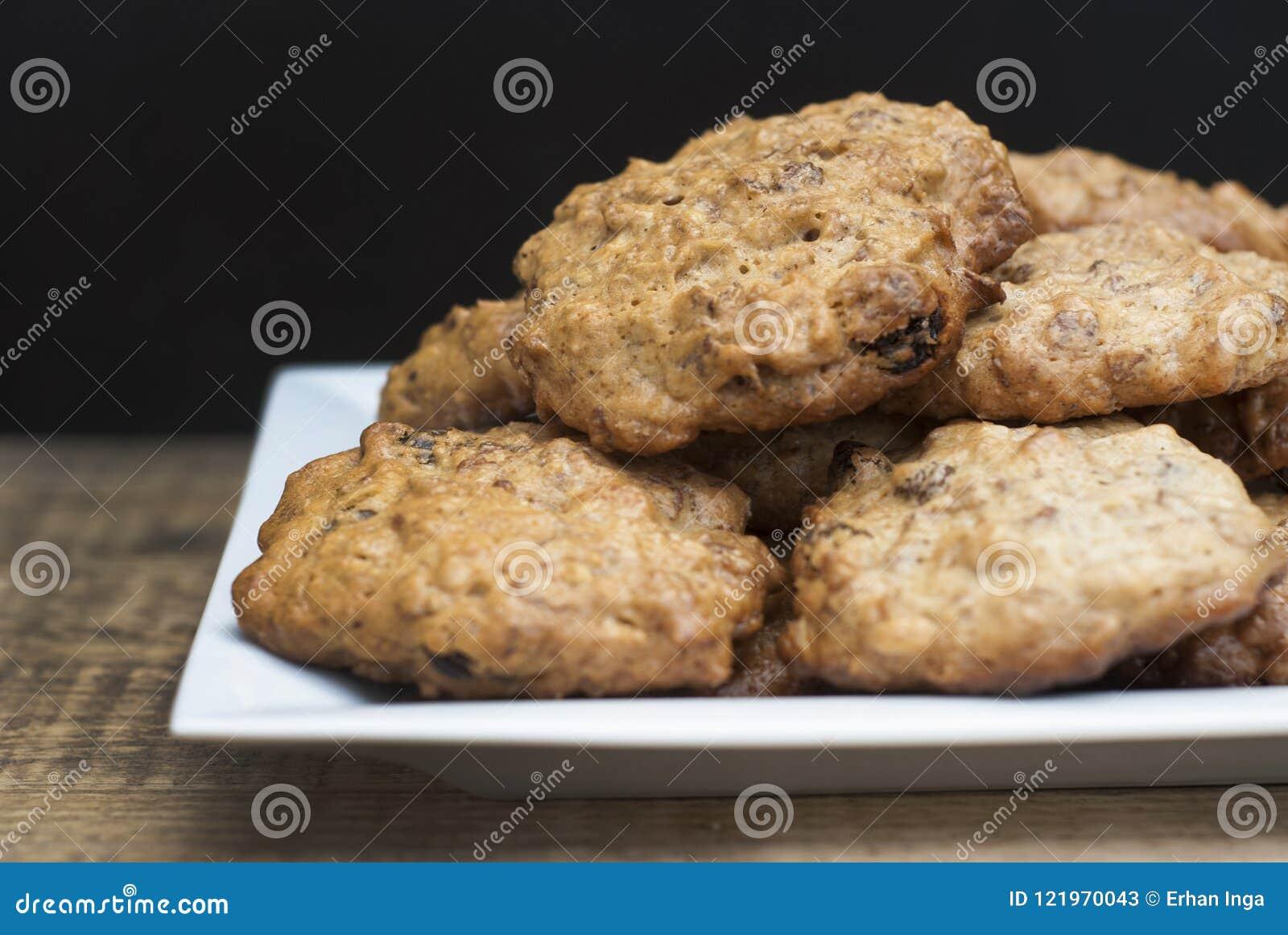 Σπιτικά oatmeal μπισκότα στο άσπρο τετραγωνικό πιάτο, στον ξύλινο πίνακα και το μαύρο υπόβαθρο Γλυκό πρόχειρο φαγητό επιδορπίων,