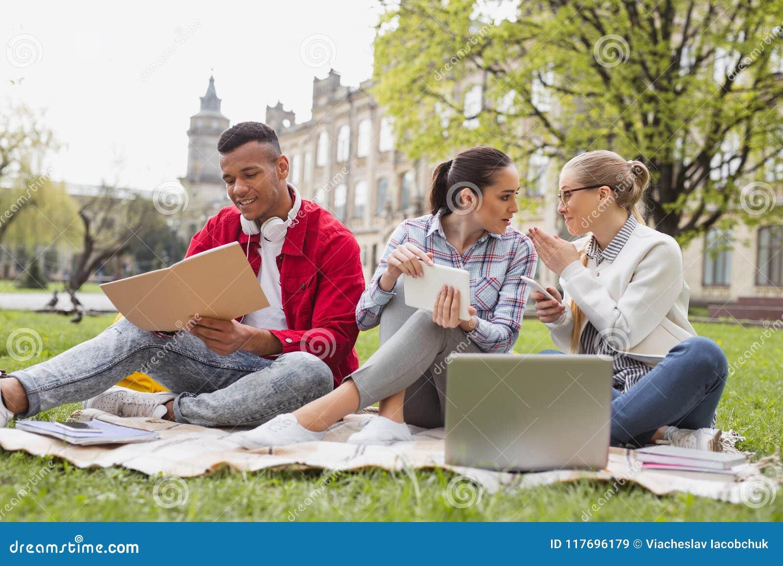 Σπουδαστές ανταλλαγής που κουβεντιάζουν ο ένας με τον άλλον ελεύθερος χρόνος εξόδων από κοινού