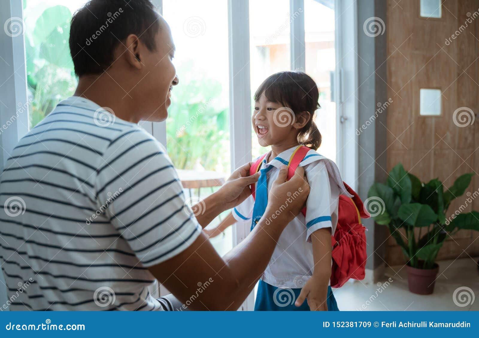 Σπουδαστής παιδικών σταθμών που φορά τη σχολική στολή που ενισχύεται από τον πατέρα της