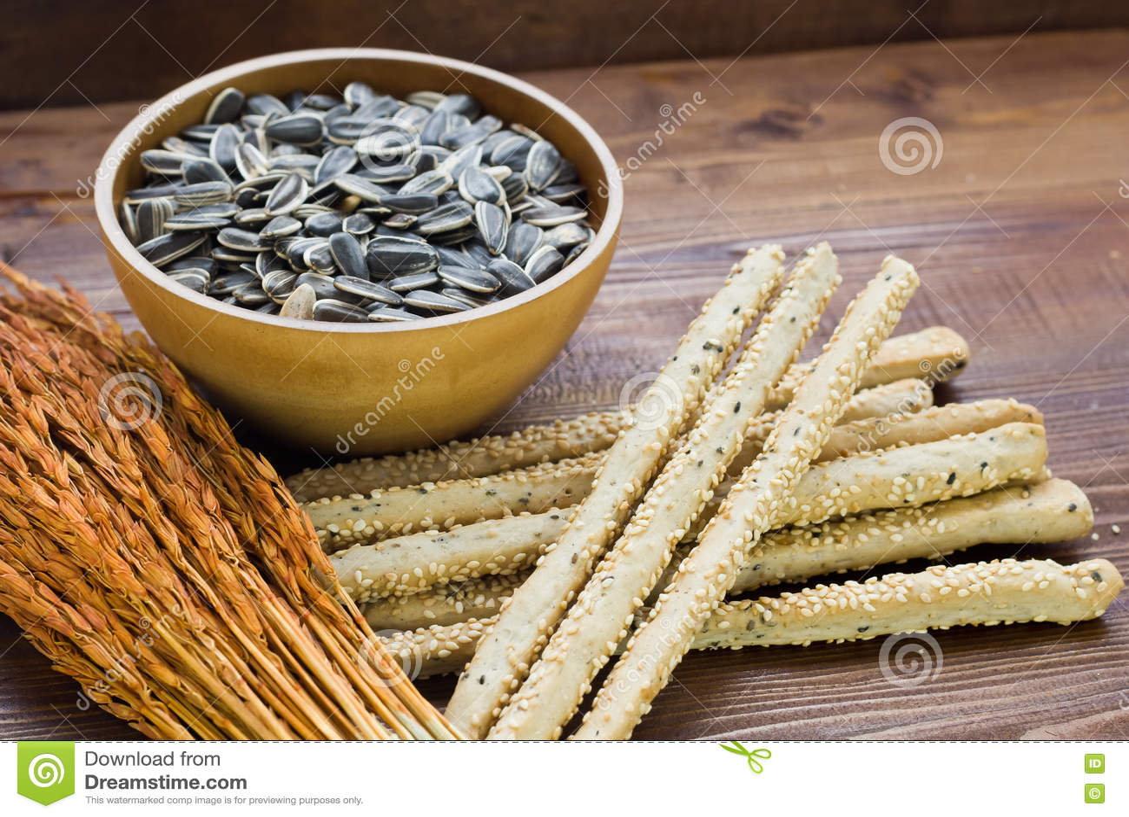 Σπόροι ηλίανθων σε ένα ξύλινο κύπελλο, το αυτί του ρυζιού, και ολόκληρα τα ραβδιά σίτου