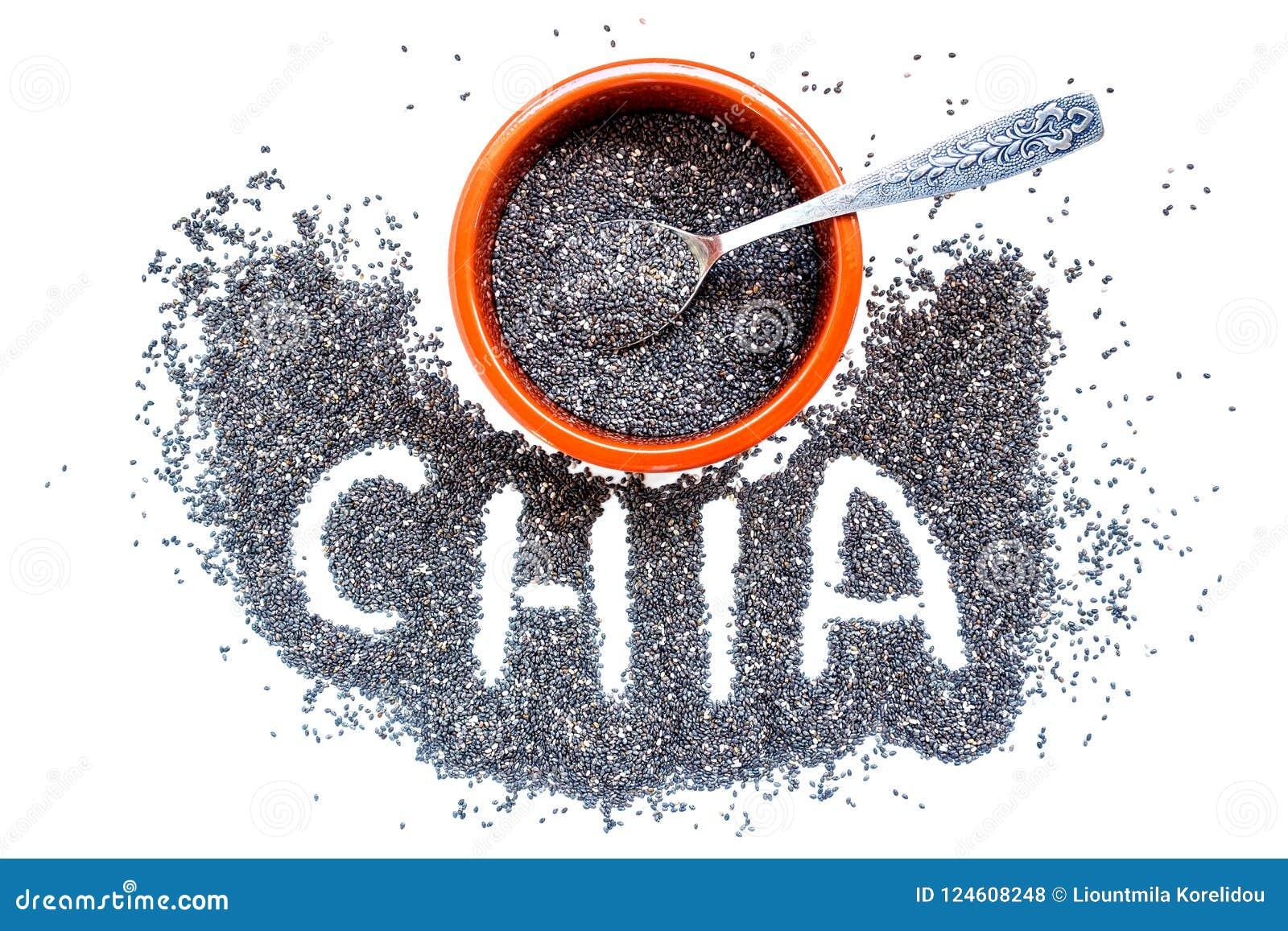 Σπόροι Chia σε ένα κεραμικό κύπελλο και ένα μικρό ασημένιο κουτάλι