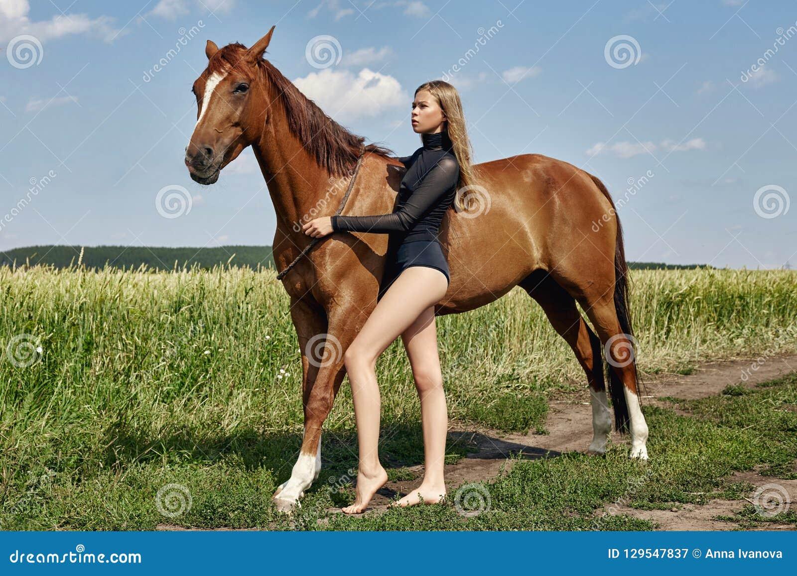 Στάσεις αναβατών κοριτσιών δίπλα στο άλογο στον τομέα Το πορτρέτο μόδας μιας γυναίκας και οι φοράδες είναι άλογα στο χωριό στη χλ