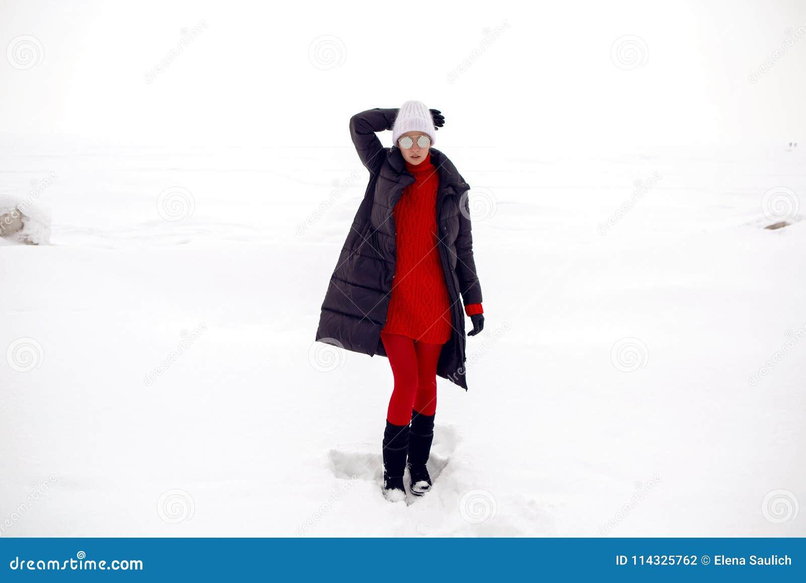 Στάσεις κοριτσιών σε έναν χιονώδη τομέα σε ένα σακάκι